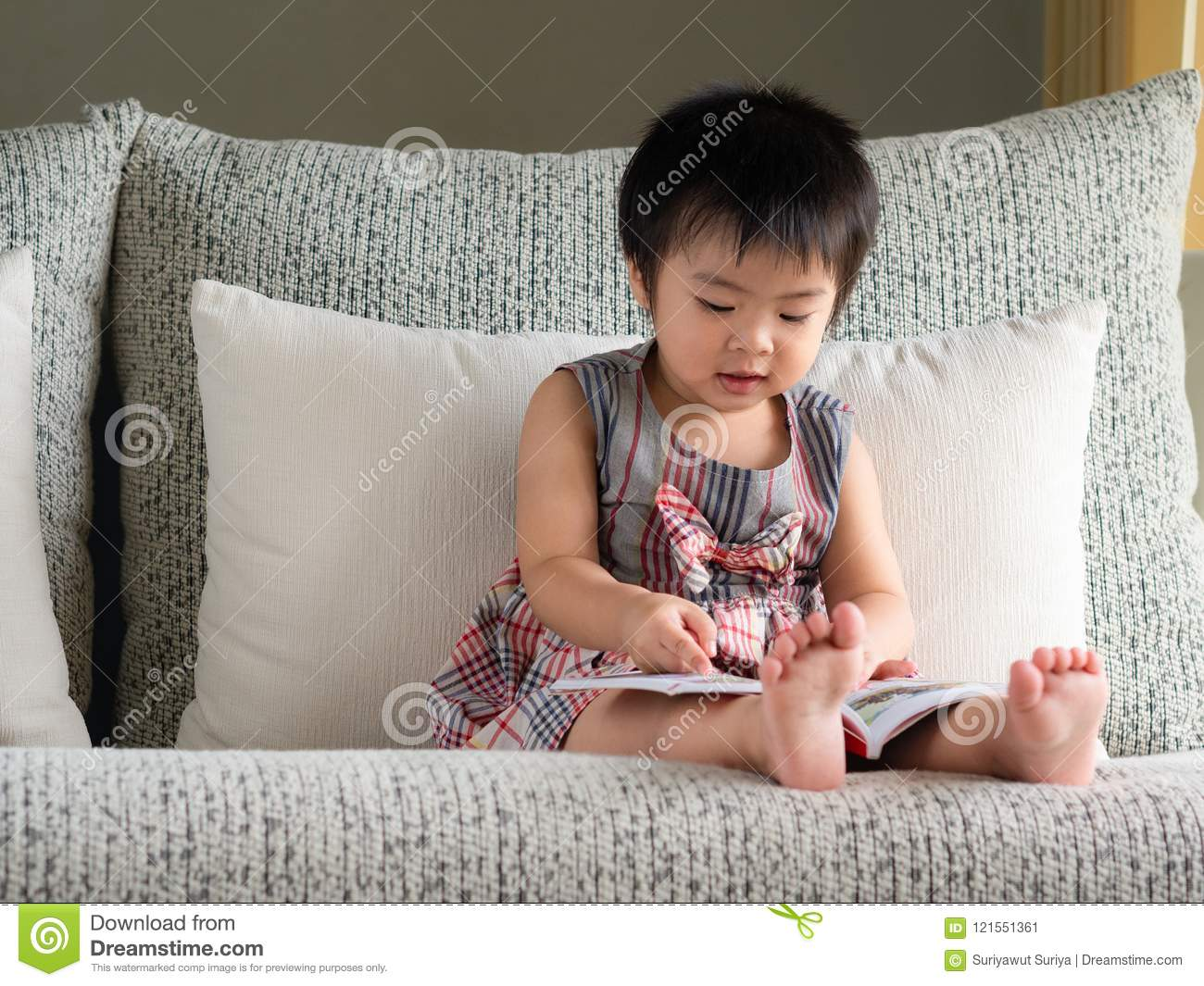 Happy little cute girl is reading the book on the white sofa. Ed