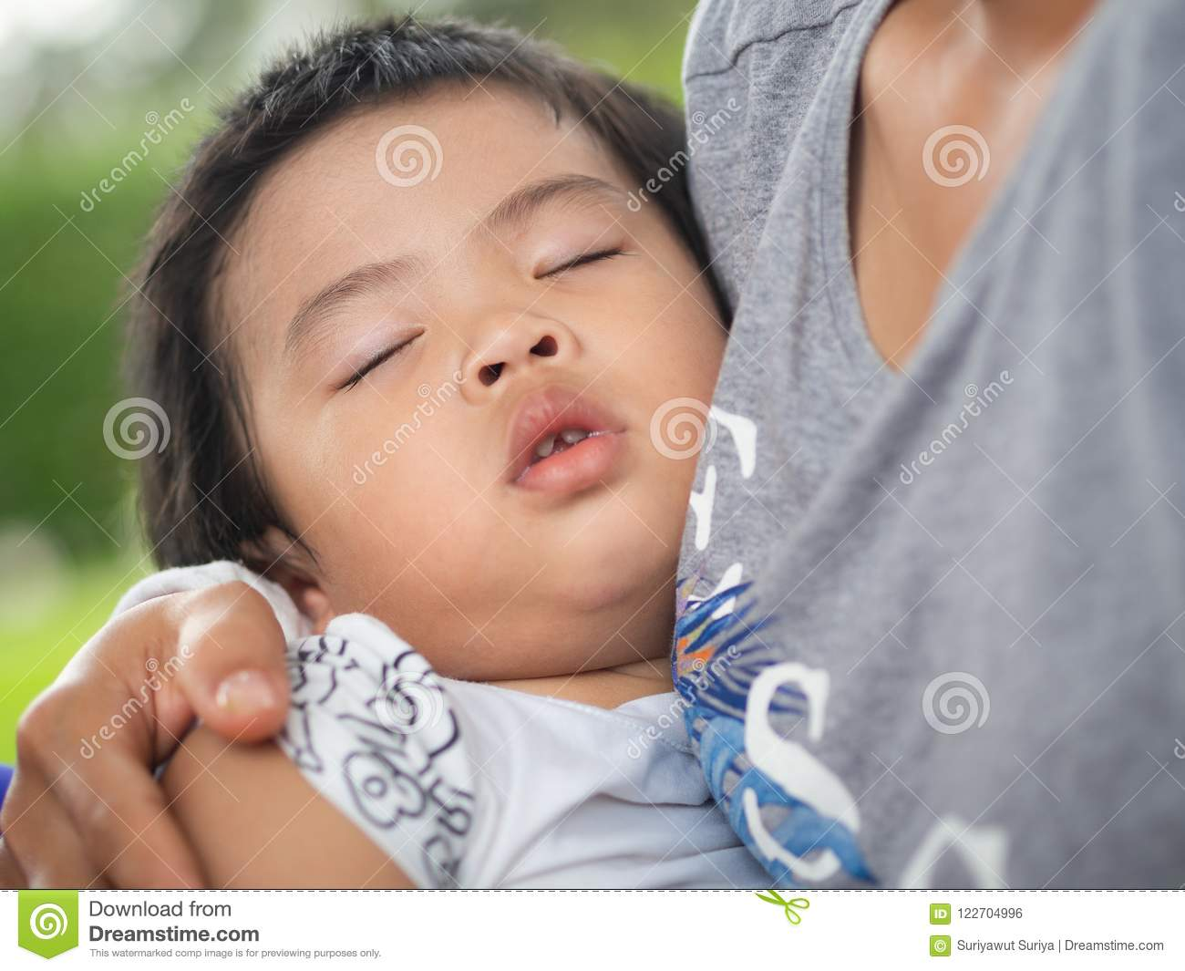 Happy Little cute girl sleeping in mother`s hug in the park. Family, Love, Happy Concept.