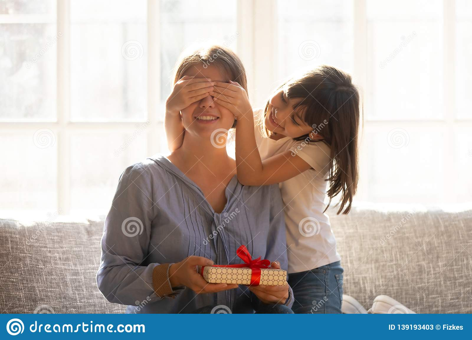 Happy Little Daughter Covering Eyes Congratulating Mom Holding Birthday Present