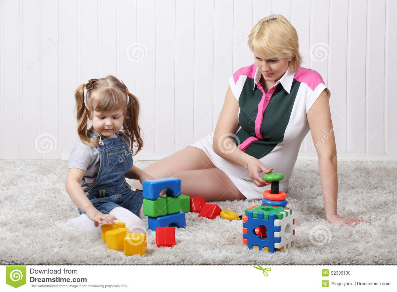 Mom Play Toys : Happy little daughter and her pregnant mother play toys