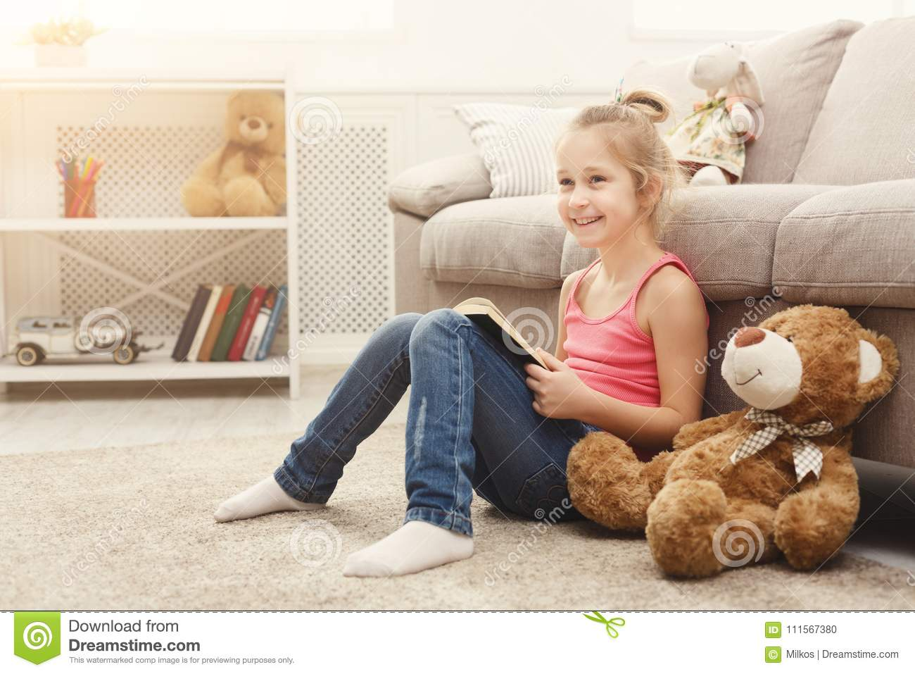 Happy little female child and her teddy bear reading book on the floor at home