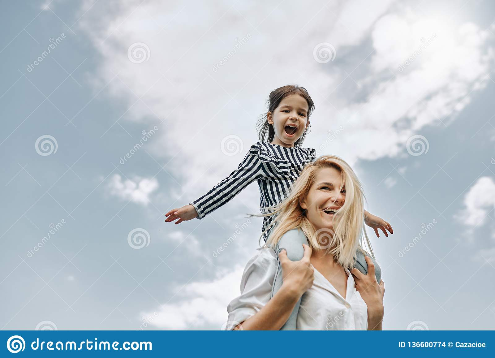 Happy little funny daughter on a piggy back ride with her happy mother on the sky background. Loving woman and her little girl