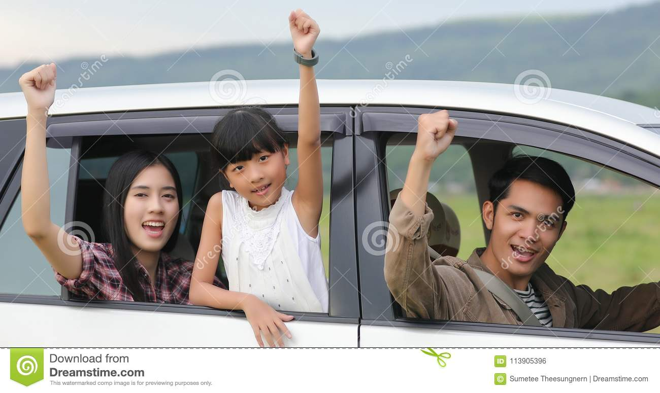 Happy little girl with asian family sitting in the car for enjo