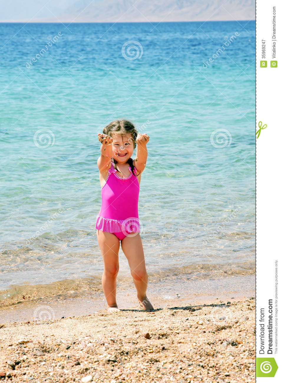 Happy little girl on the beach playing