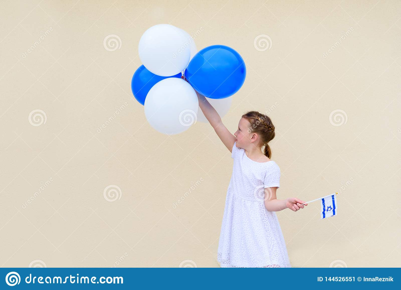 Happy little girl with blue and white balloons ans Israel flag.