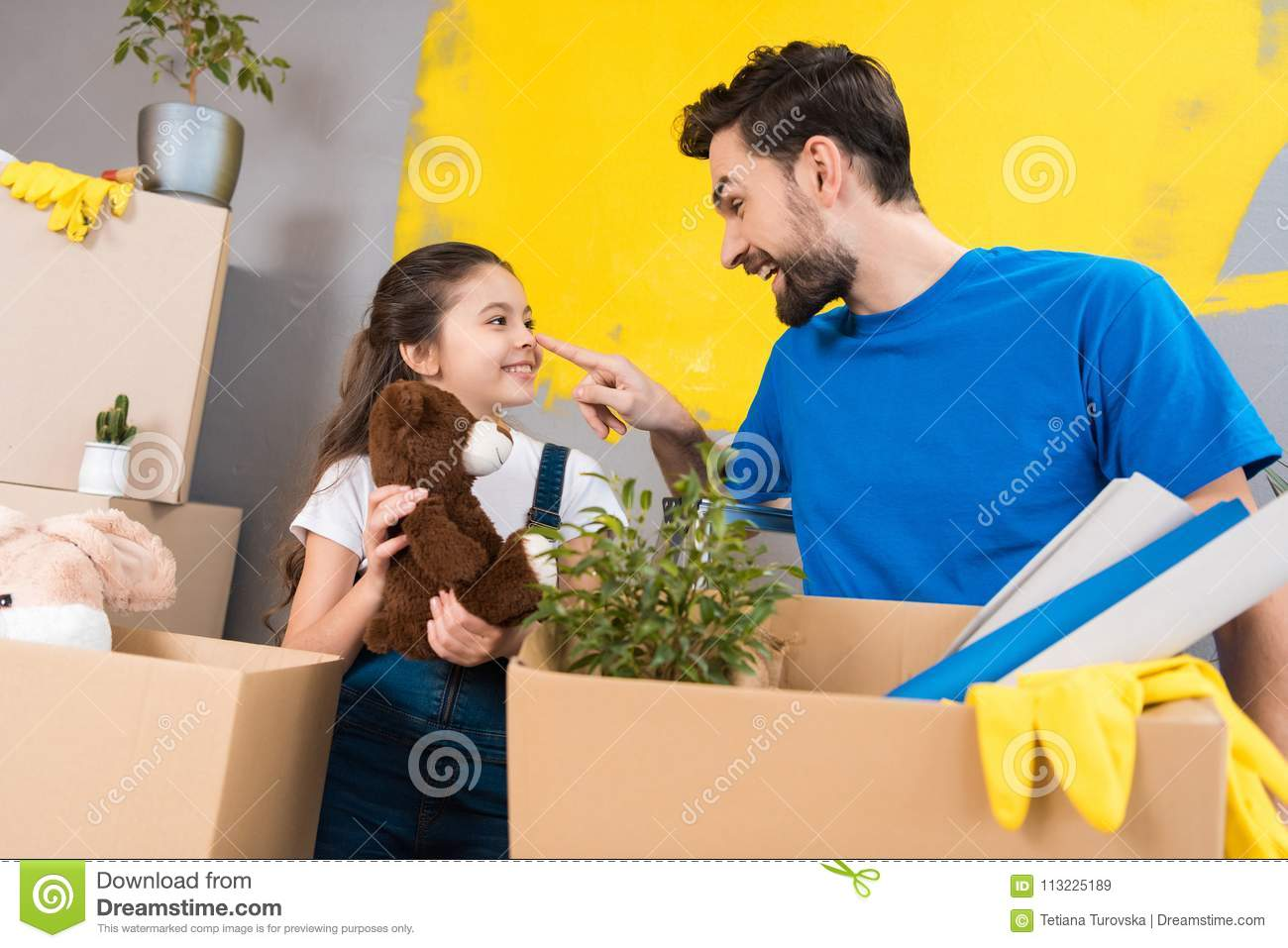 Happy little girl with box of plush toys looks at father which started repair in house.