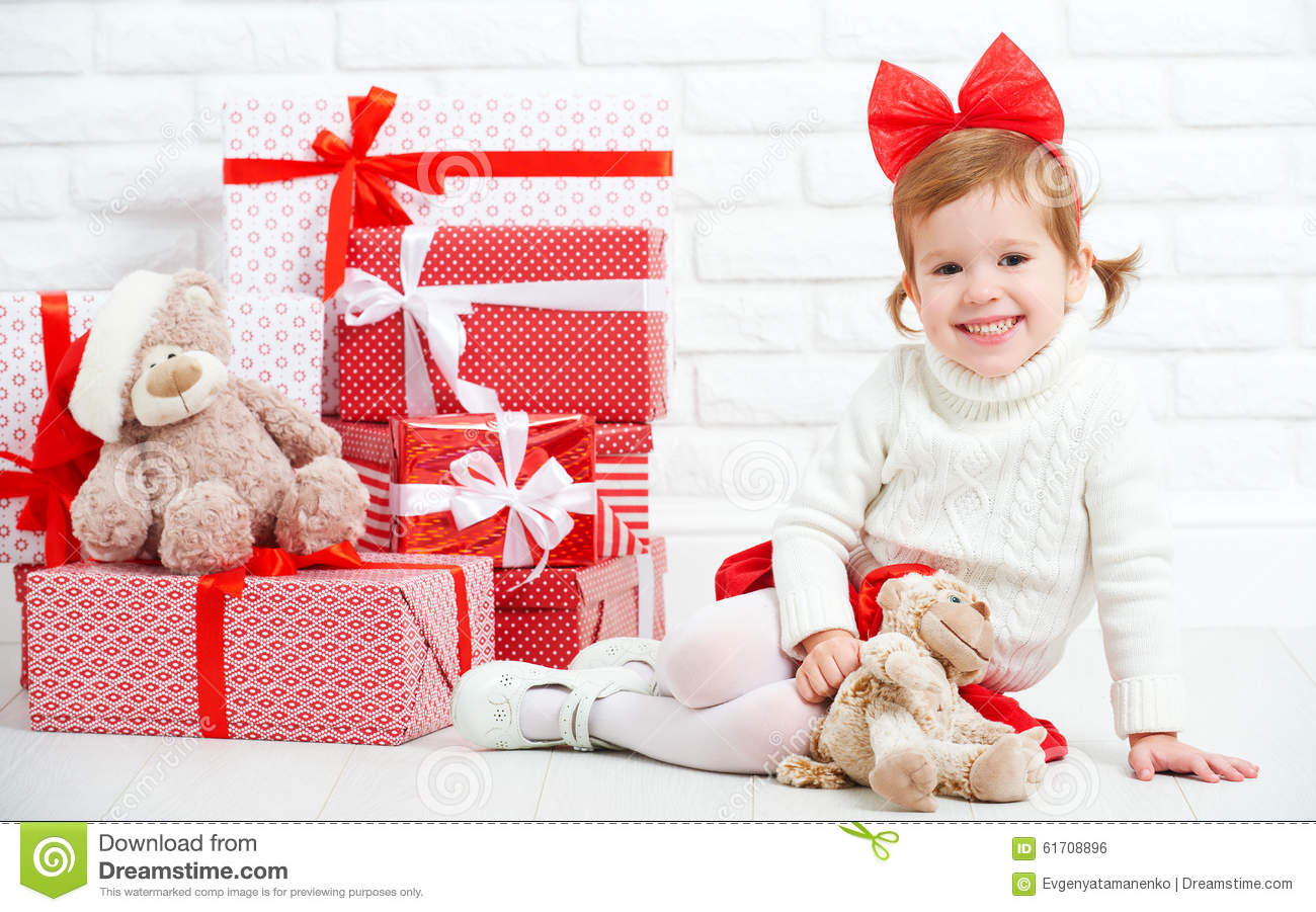Happy little girl child with Christmas gifts at wall