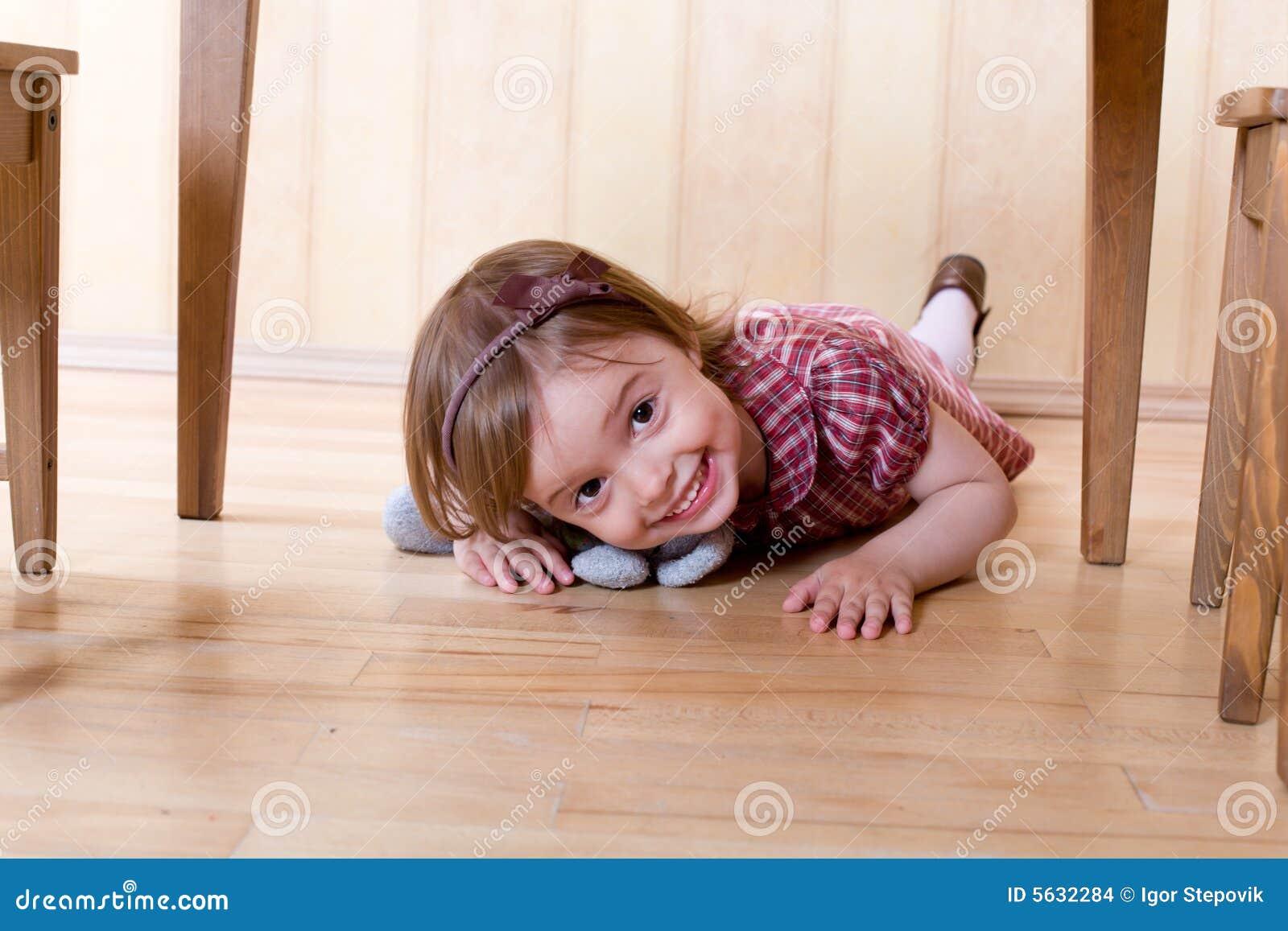 Happy Little Girl Crawling On The Hardwood Floor Stock