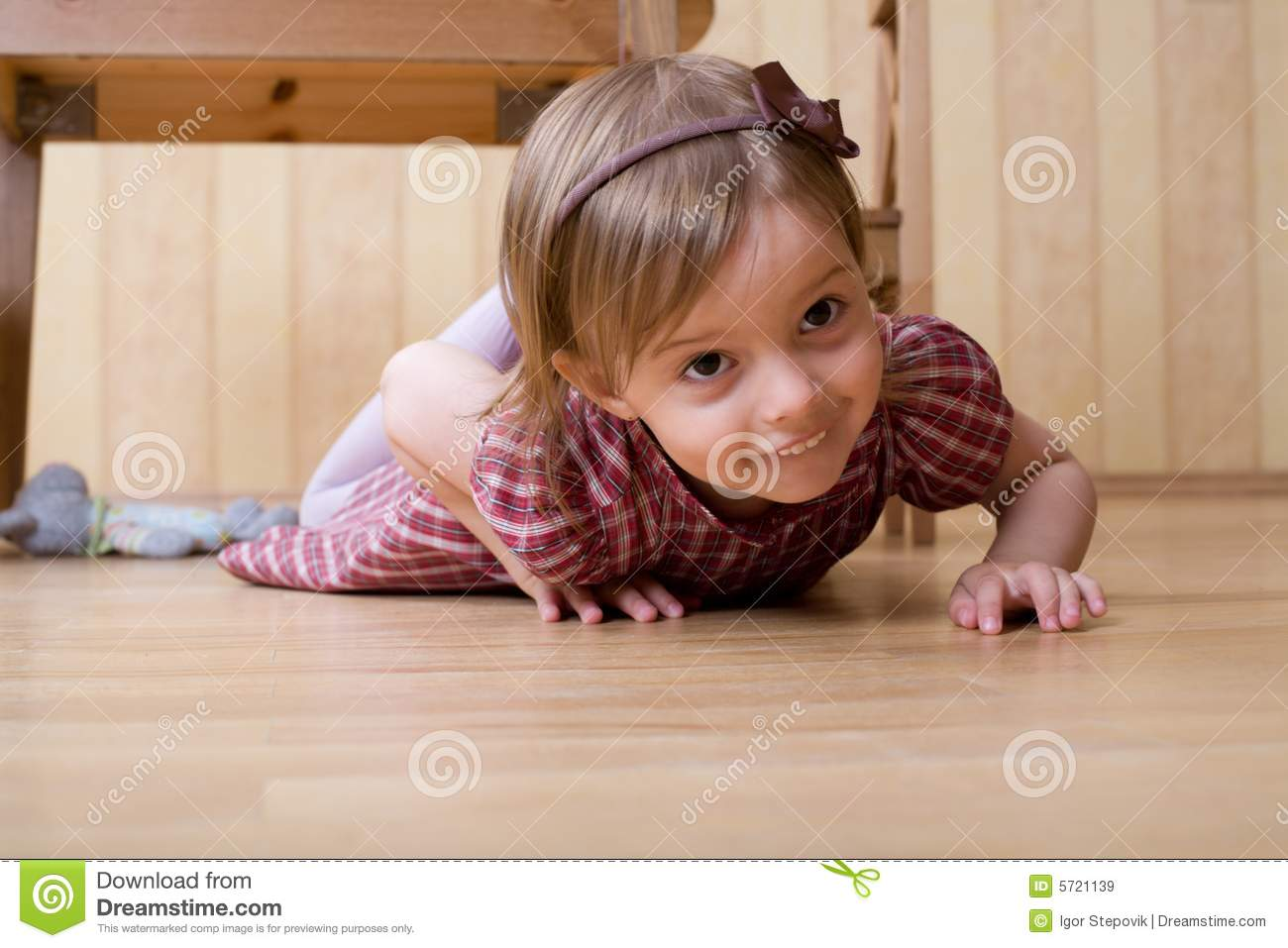 Happy Little Girl Crawling On The Hardwood Floor Royalty