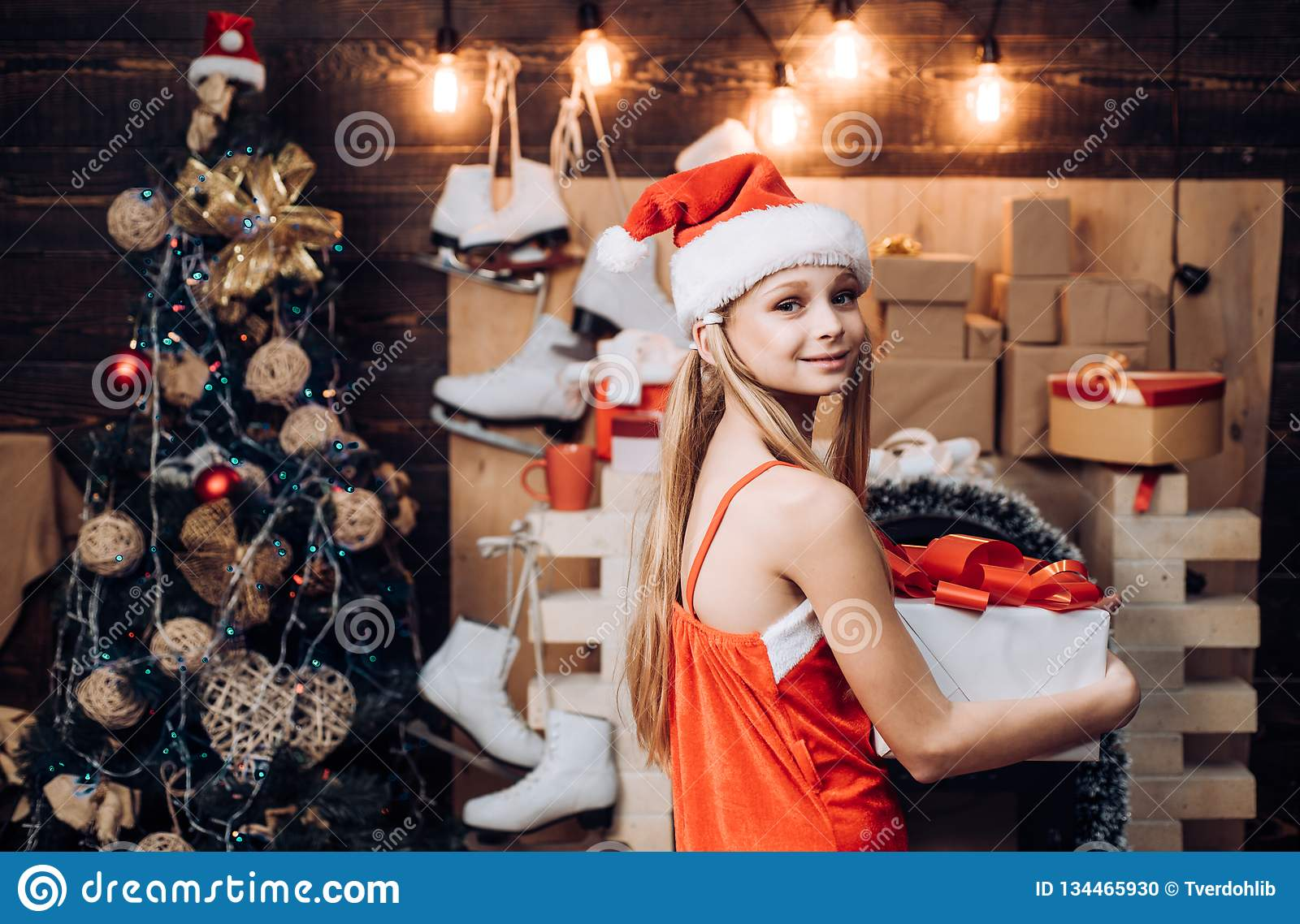 Happy little girl dressed in winter clothing think about Santa near Christmas tree. Teenager Christmas. Winter evening