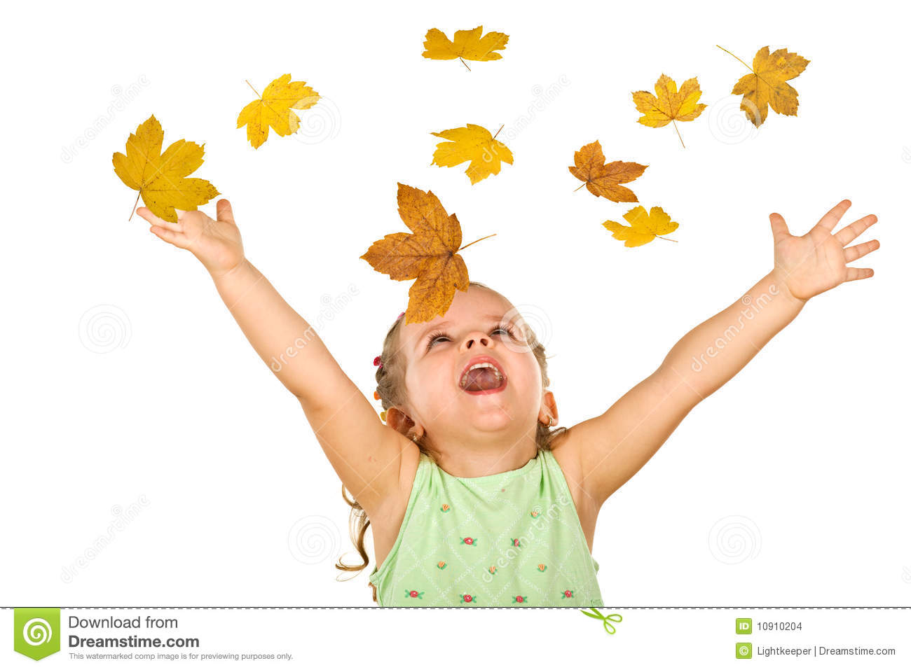 Happy little girl with falling autumn leaves