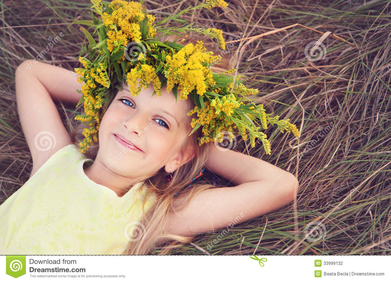 Happy little girl in flowers crown laying on the grass stock photo happy little girl in flowers crown laying on the grass izmirmasajfo Gallery