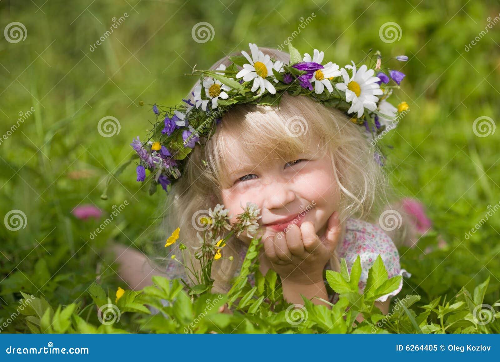 Happy little girl in flowers wreath