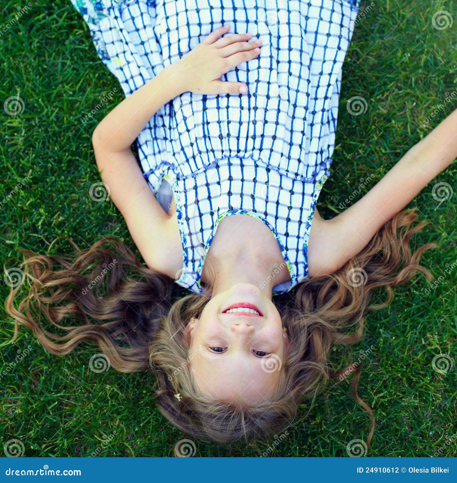 happy little girl having fun lying on grass stock photography
