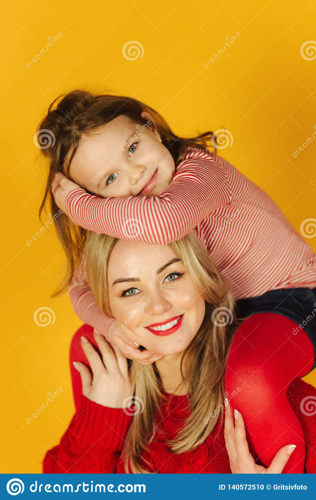 Happy little girl with her young mother on the yellow background. Daughter sitting on mom`s neck. Smile