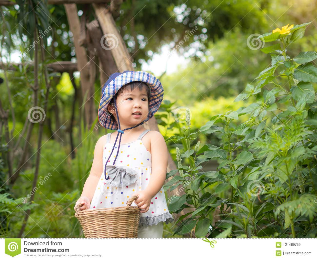 Happy little girl hold the basket in the farm. Farming & Children Concept.