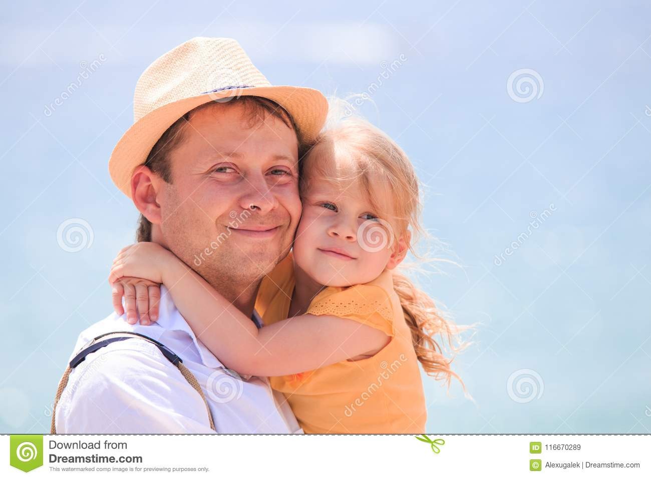 Happy little girl hugging father. Cheerful young man with child