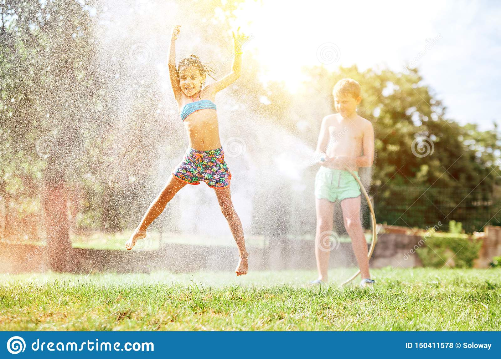 Happy little girl jumps under water, when brother pours her from garden hose. Hot summer days activity