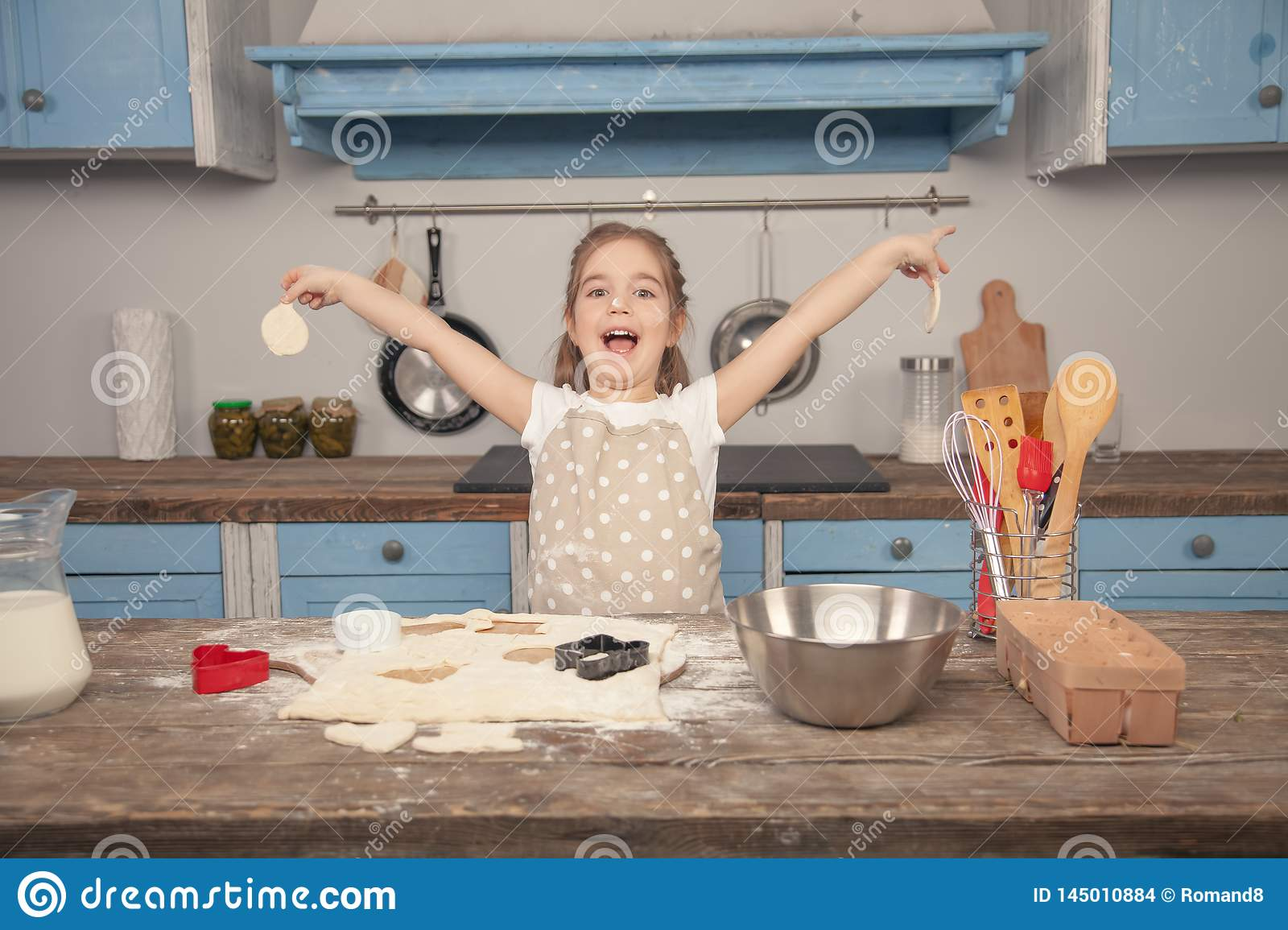 Happy little girl in the kitchen is making different shapes of cookies out of dough, helping her mom. Little helper