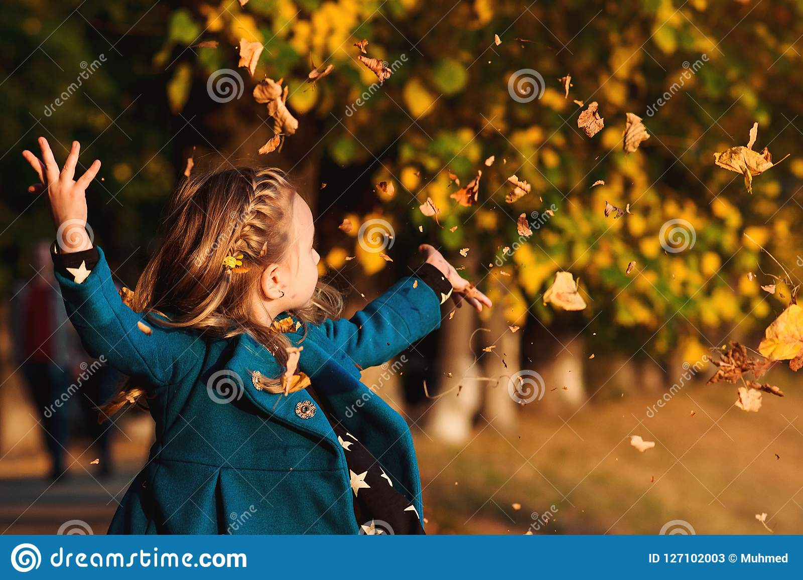 Happy little girl playing with autumn leaves. Cute child having fun in park. Stylish baby girl in blue coat throws autumn leaves o