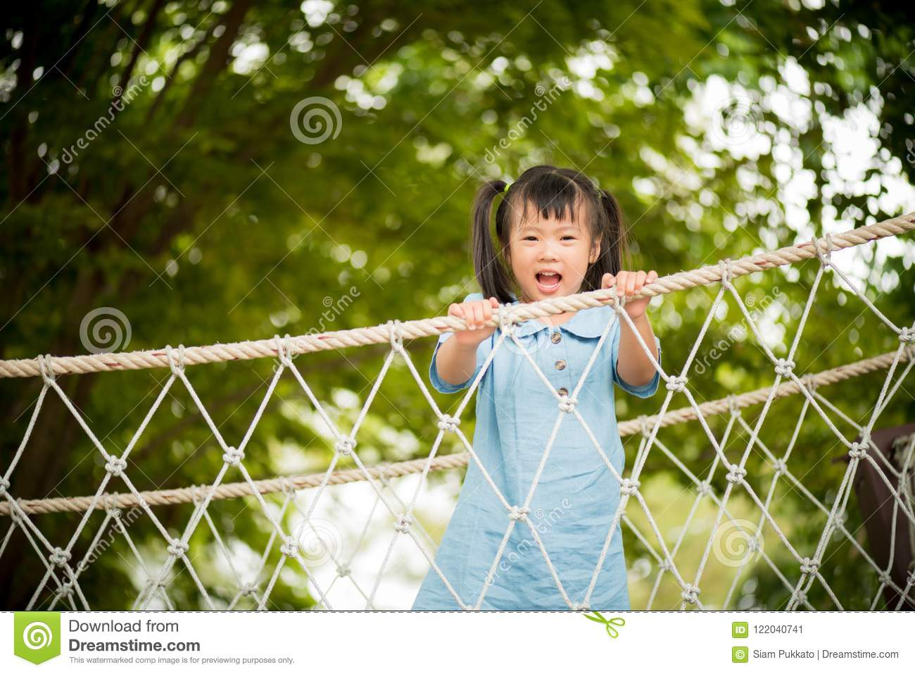 Happy Little Girl Playing Climbing On The Rope Bridge ...