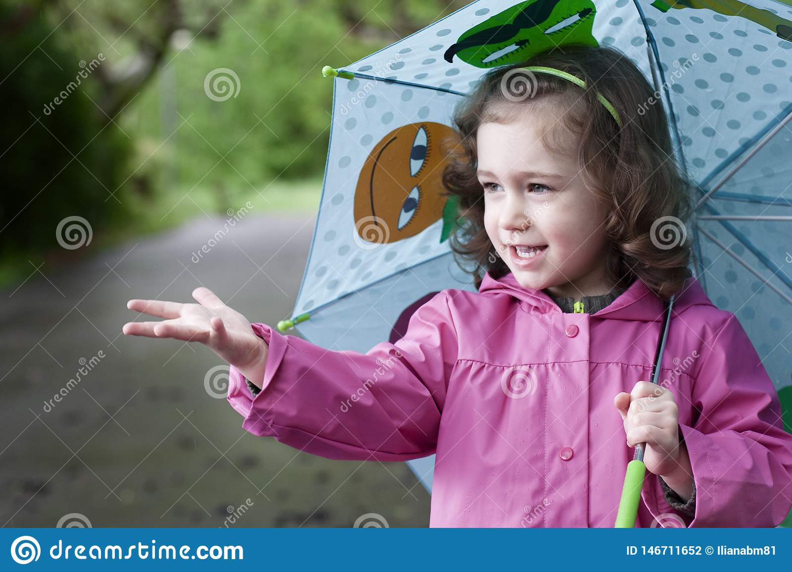 A happy little girl in a rainy day