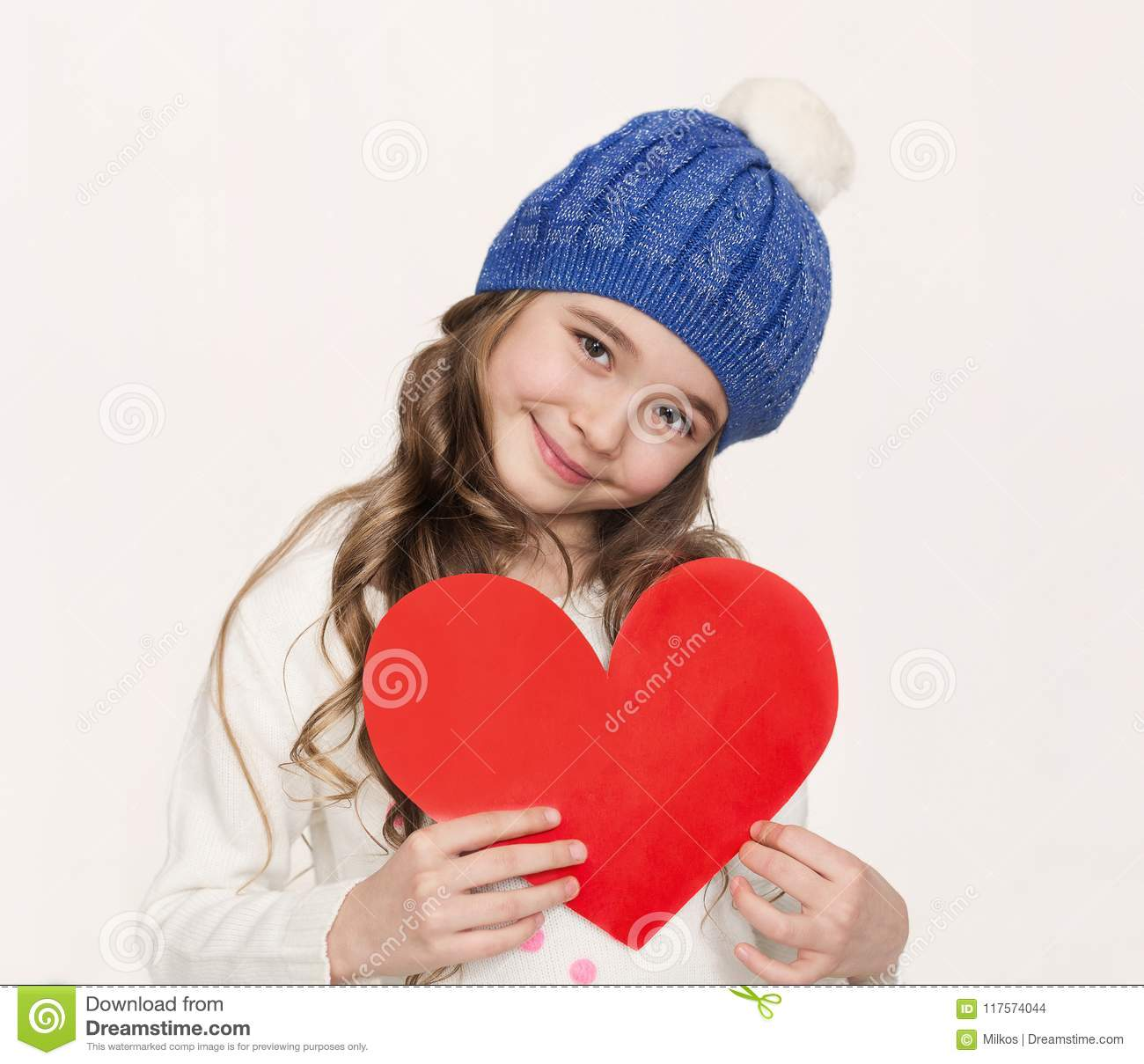 34f95379ee2 Happy little girl with red paper heart at white studio background. Portrait  of smiling child in hat with love symbol