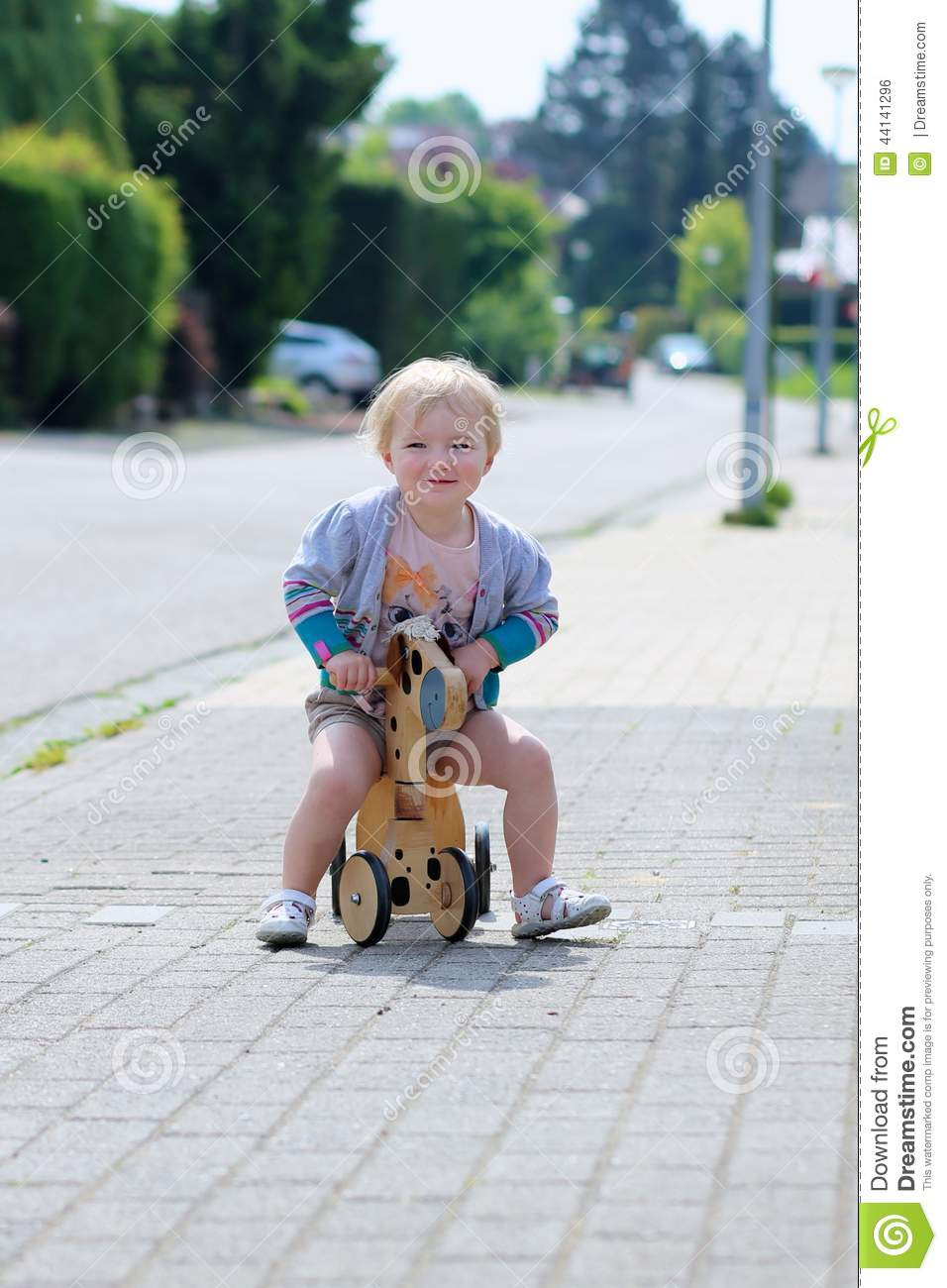 da26ab791ef Happy little kid, cute blonde toddler girl playing outdoors on the street  riding her push bike, wooden horse with three wheels, on a sunny summer day