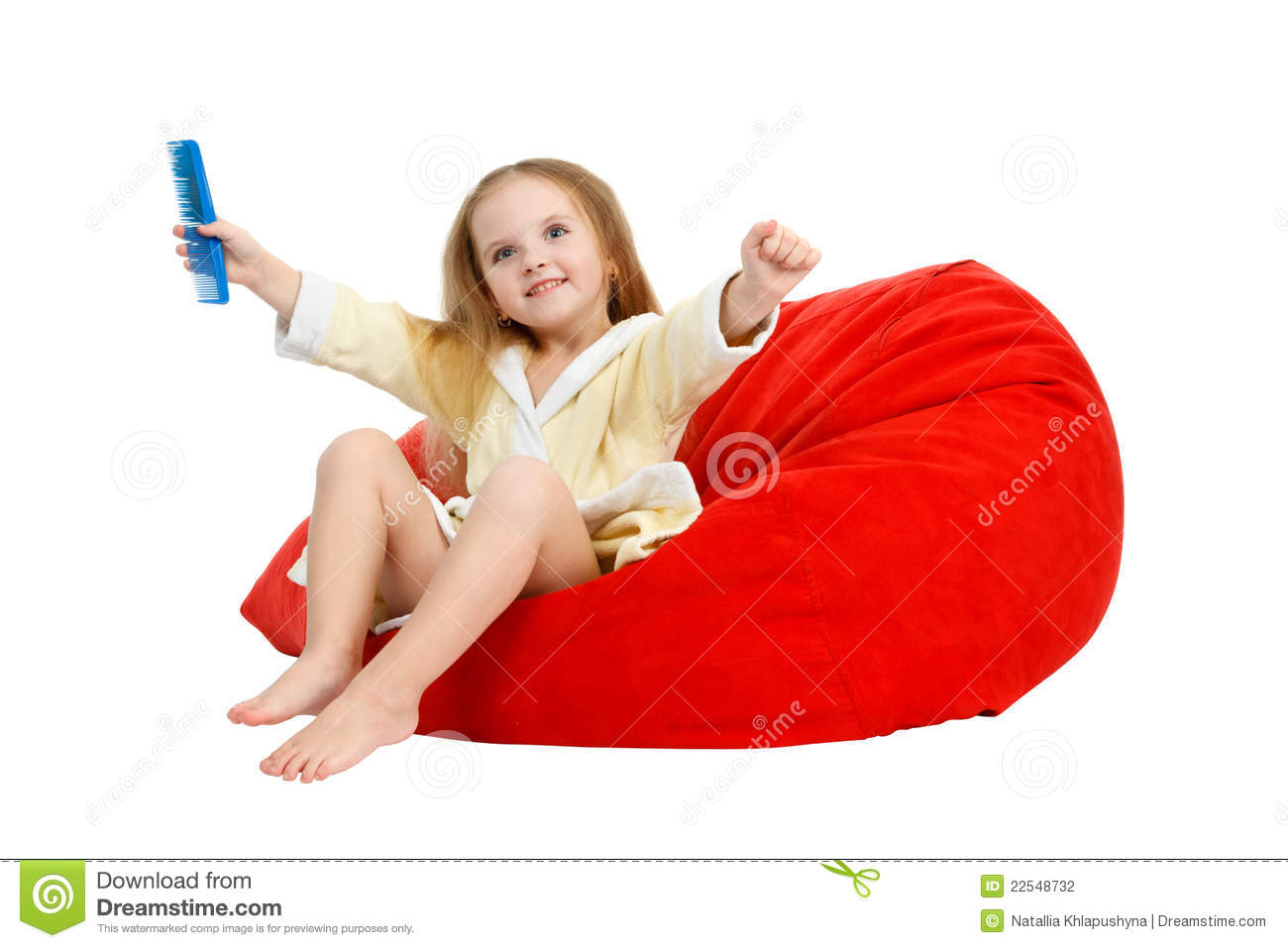 Happy little girl sitting in a chair, combing hair