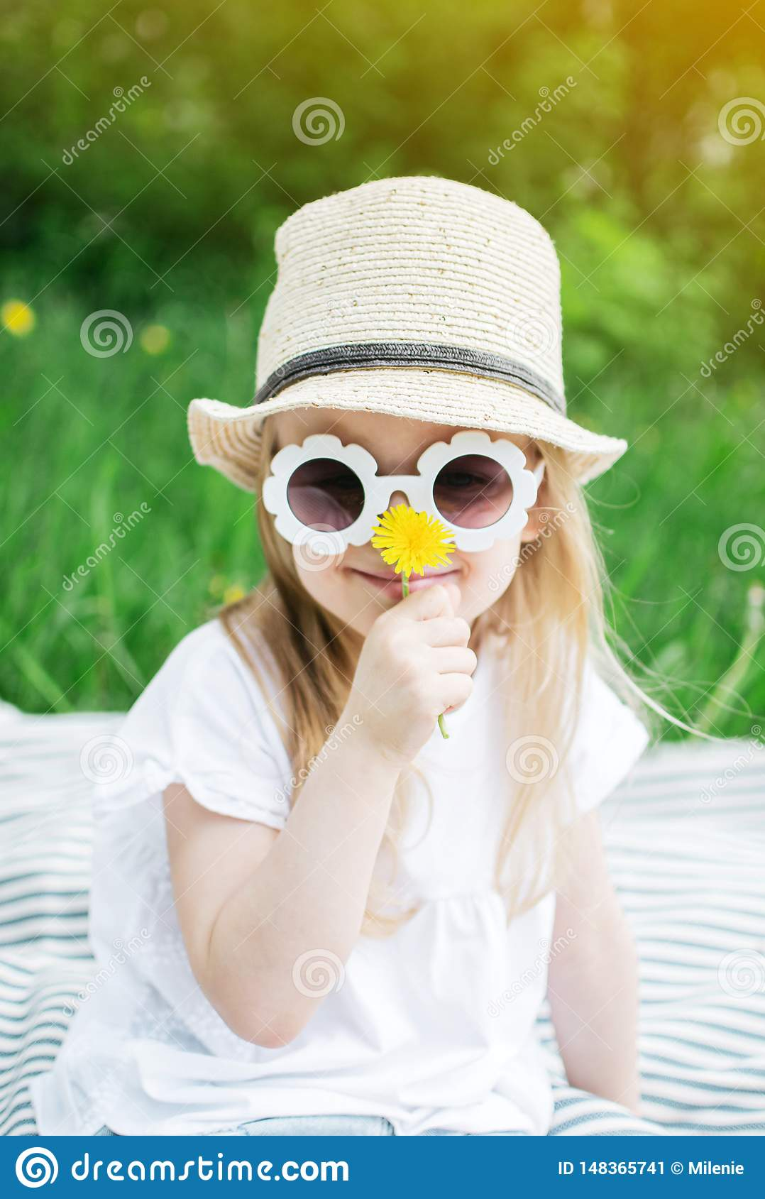 Happy little girl sitting on the green grass with flower dandelion in your hands