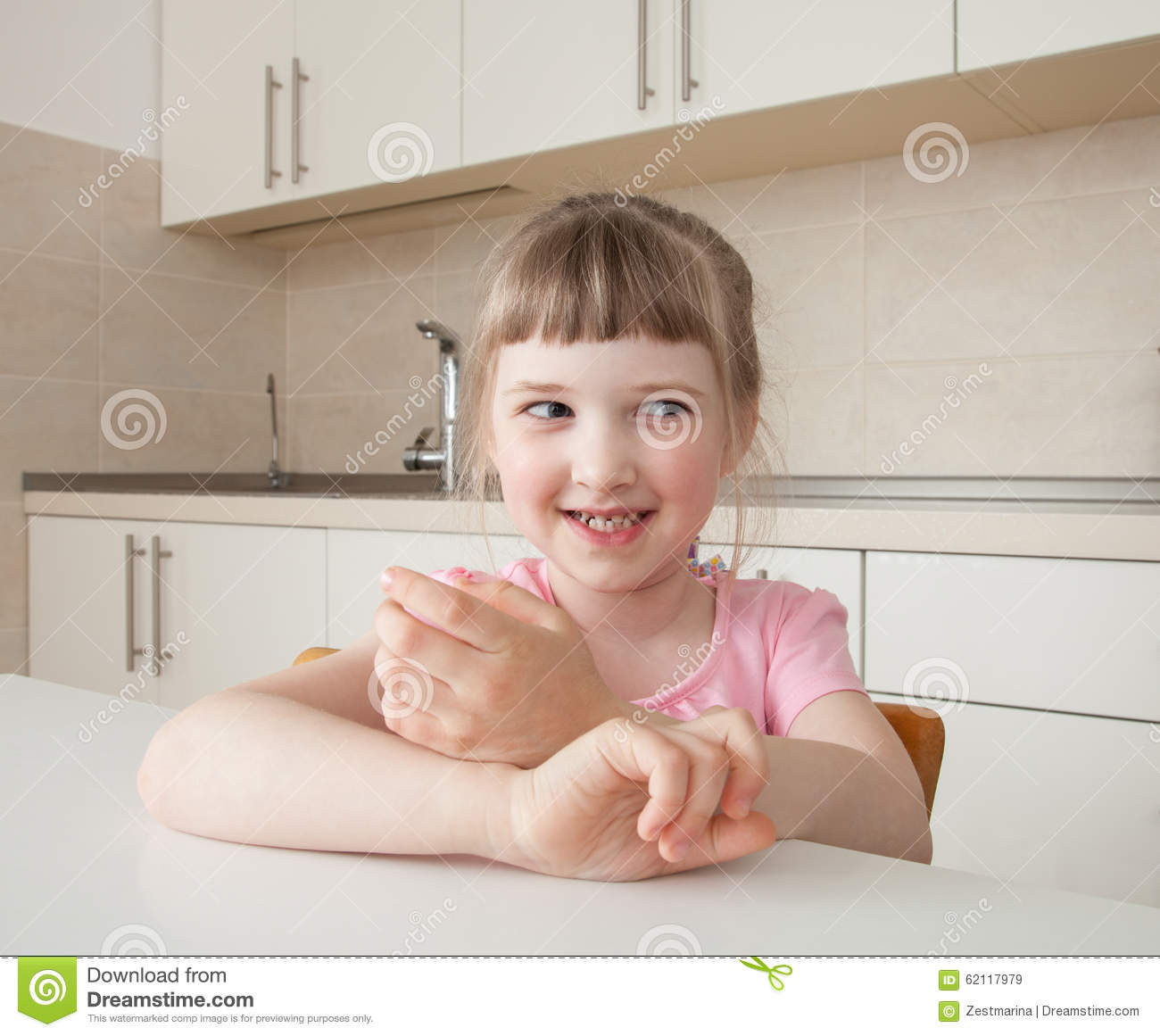 Happy Little Girl Sitting At Table Stock Photo