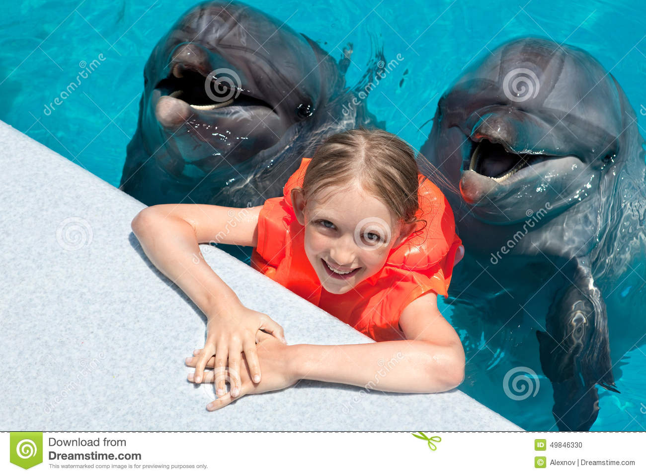 Happy Little Girl Smiling With Two Dolphins In Swimming