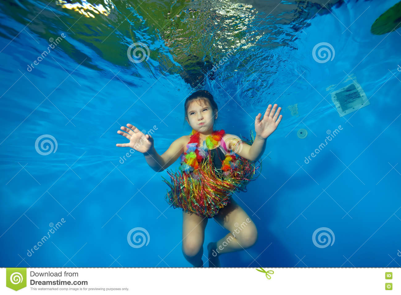 Happy Little Girl Swimming And Dancing Underwater In The Pool In