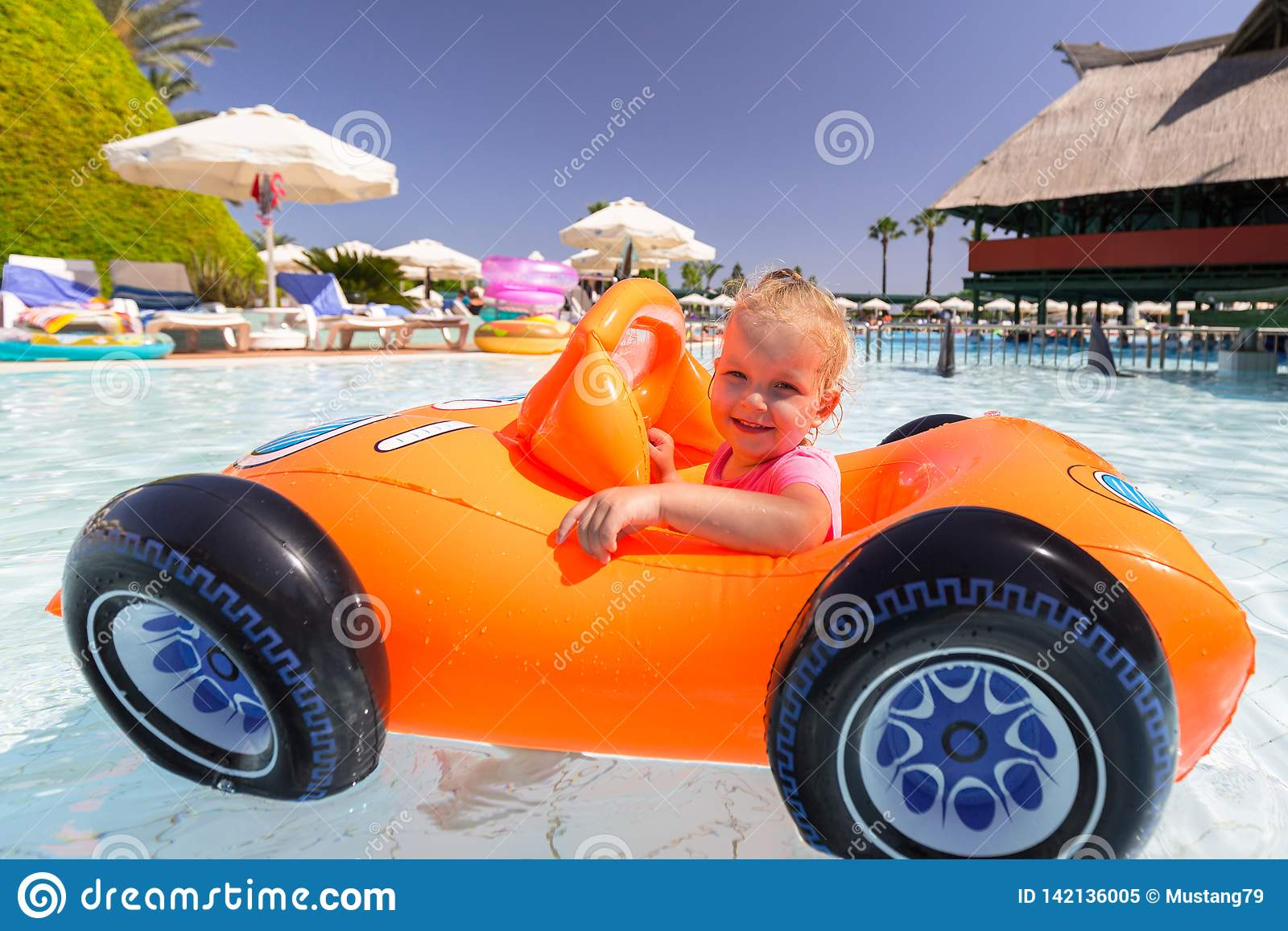Happy little girl swimming in the inflatable car on summer holidays