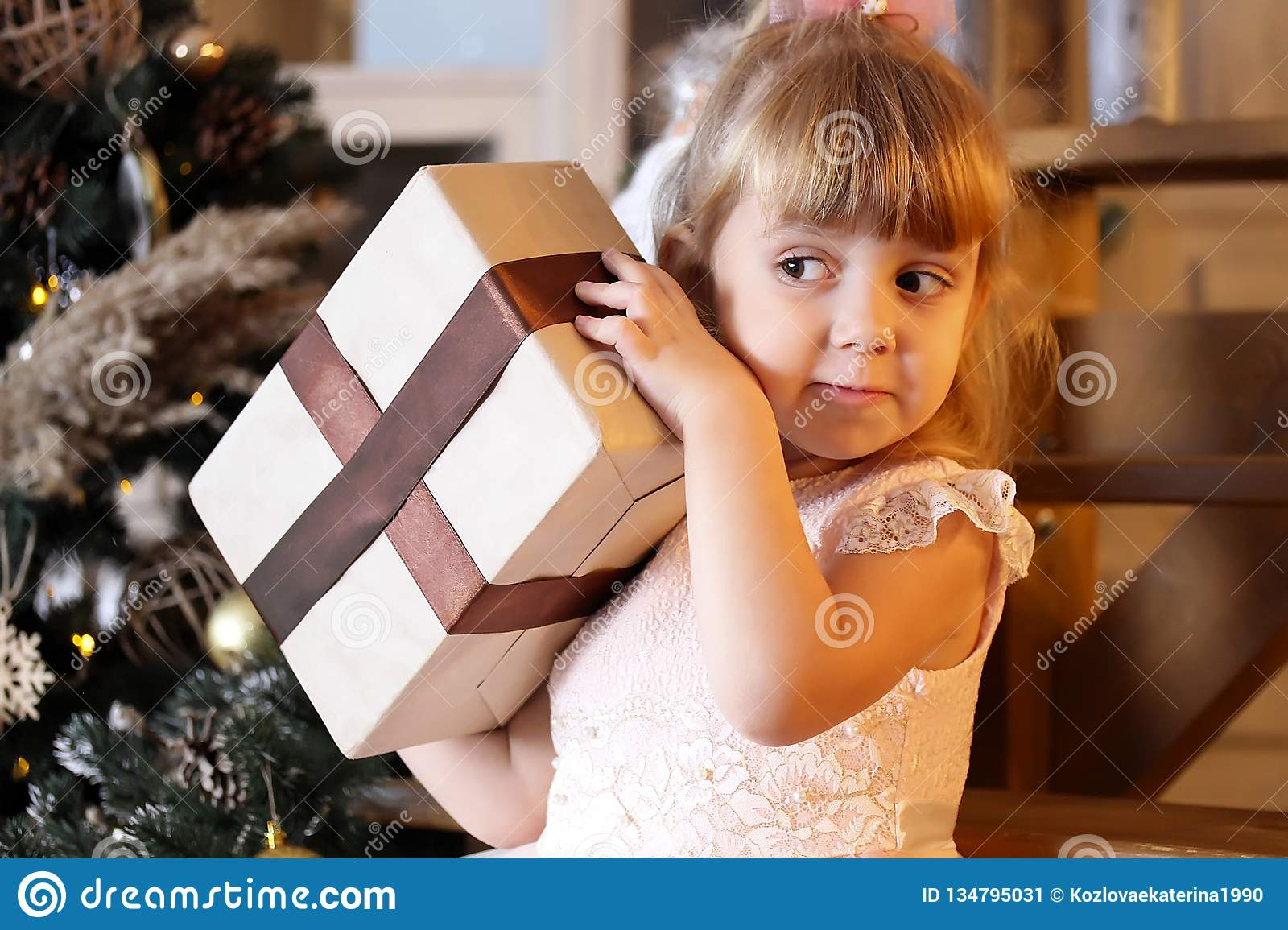 Happy little girl try to open christmas gift box