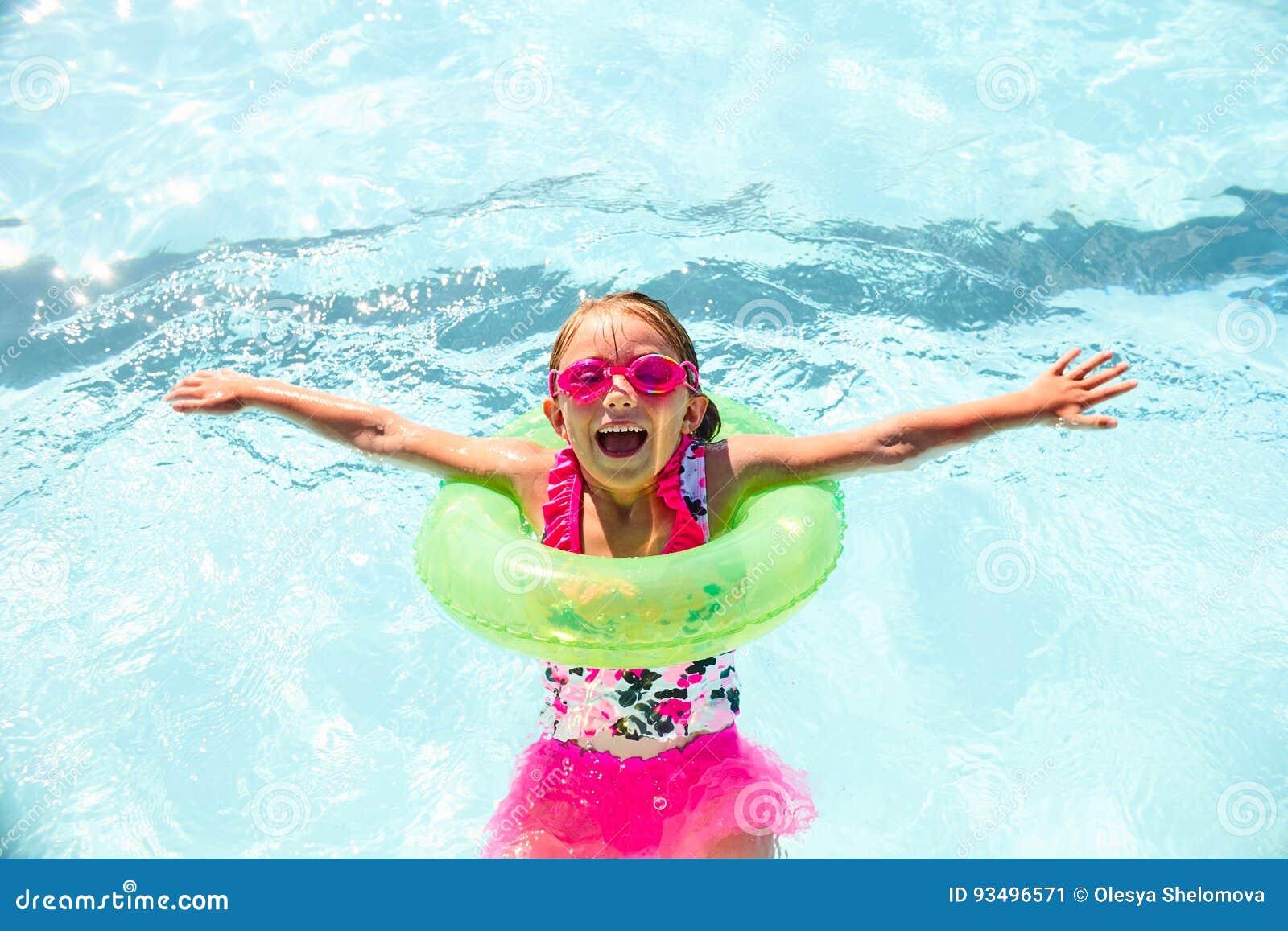 Happy little girl wearing flotation ring in pool