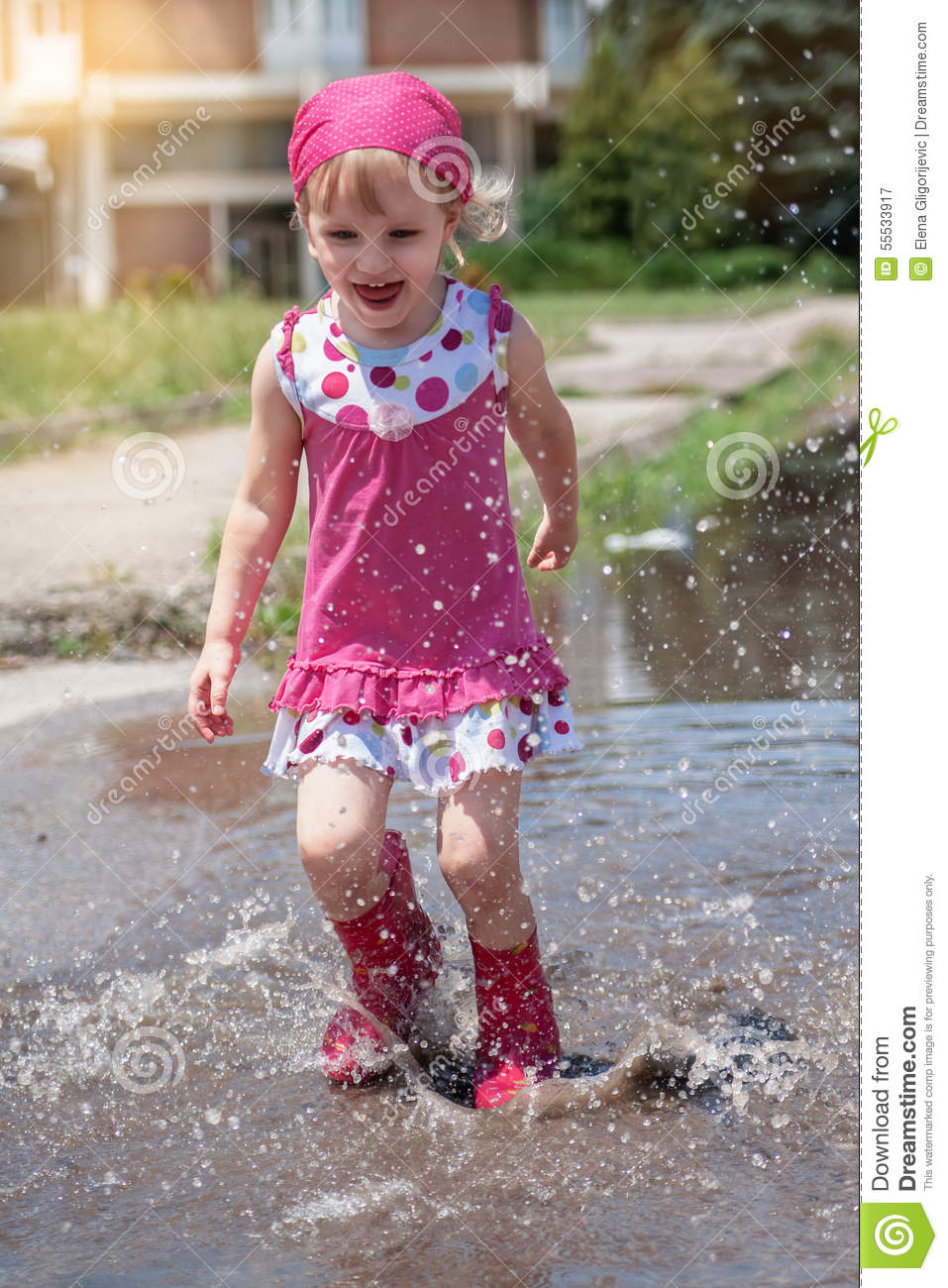 Happy Little Girl Wearing Pink Rain Boots Jumping Into