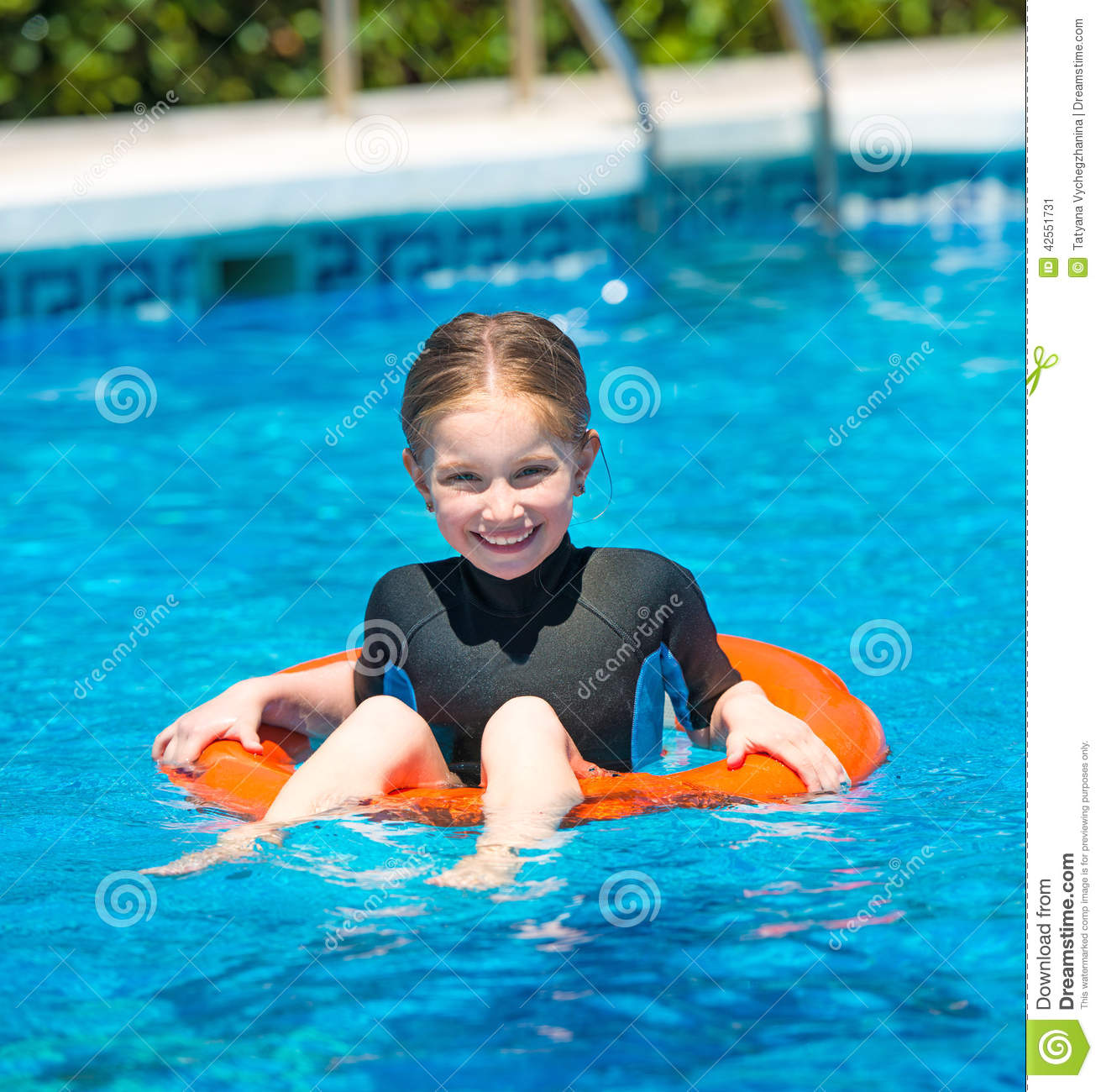 Cute little girl swims in a wetsuit with a lifeline in the pool in summer cc8d22fea