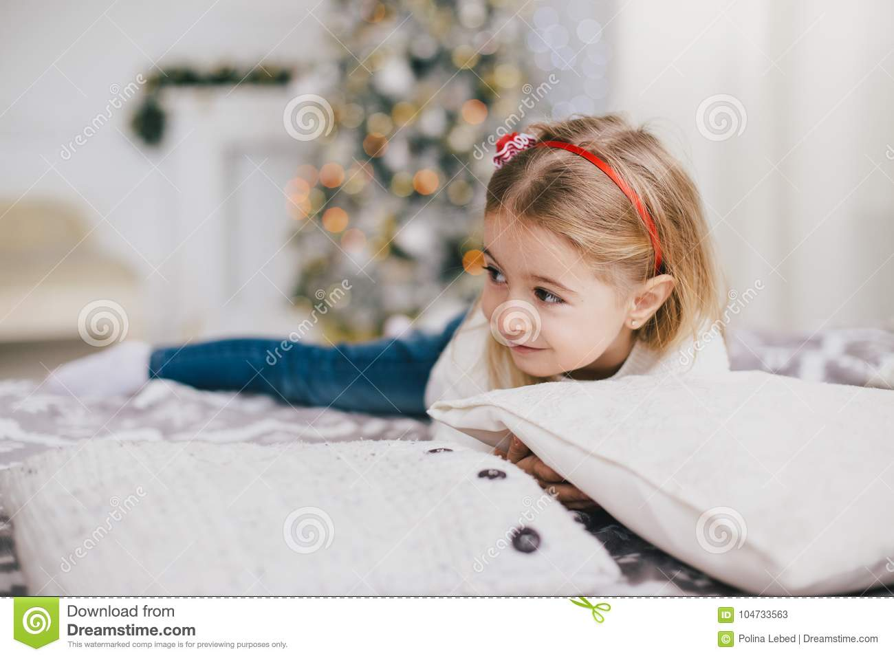 Happy Little Girl In A White Sweater And Blue Jeans Posing Near