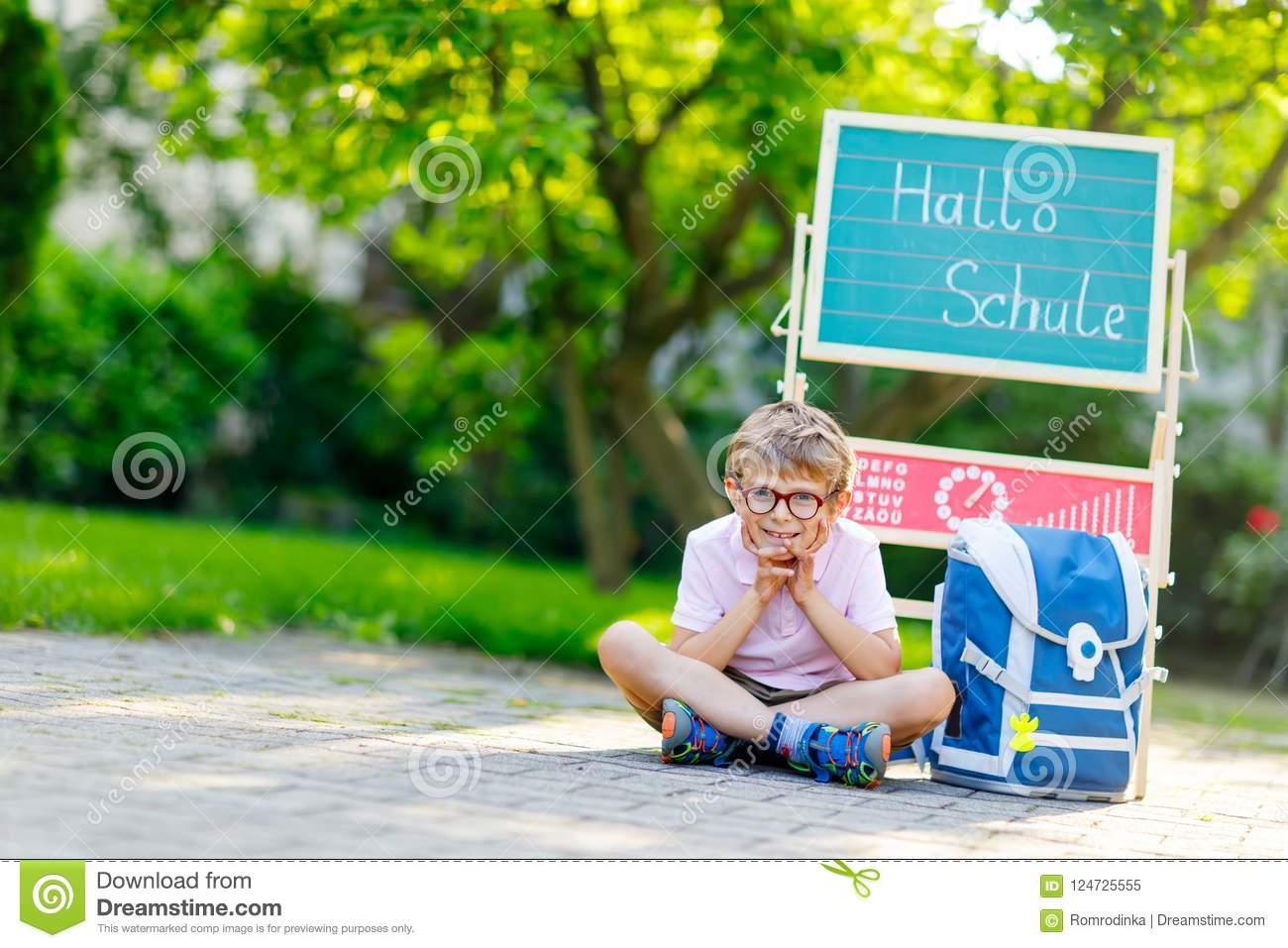 Happy little kid boy with glasses sitting by desk and backpack or satchel. Schoolkid with traditional German school bag