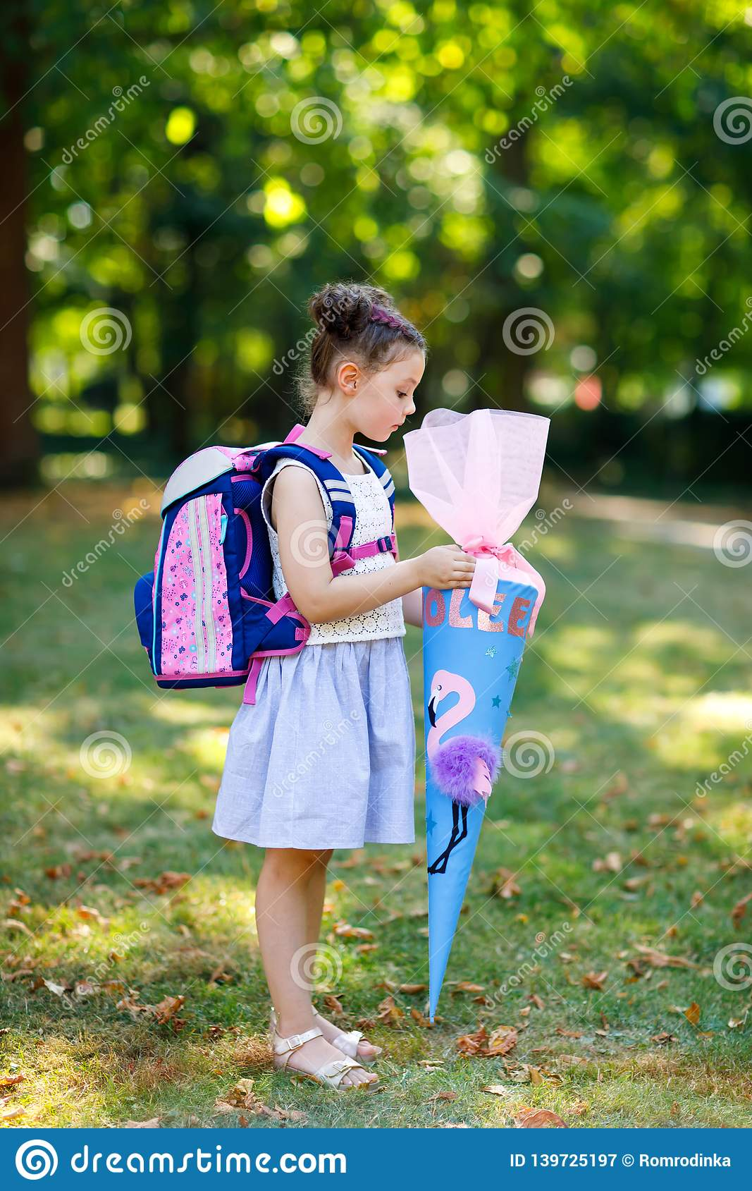 Happy little kid girl with backpack or satchel and big school bag or cone traditional in Germany for the first day of