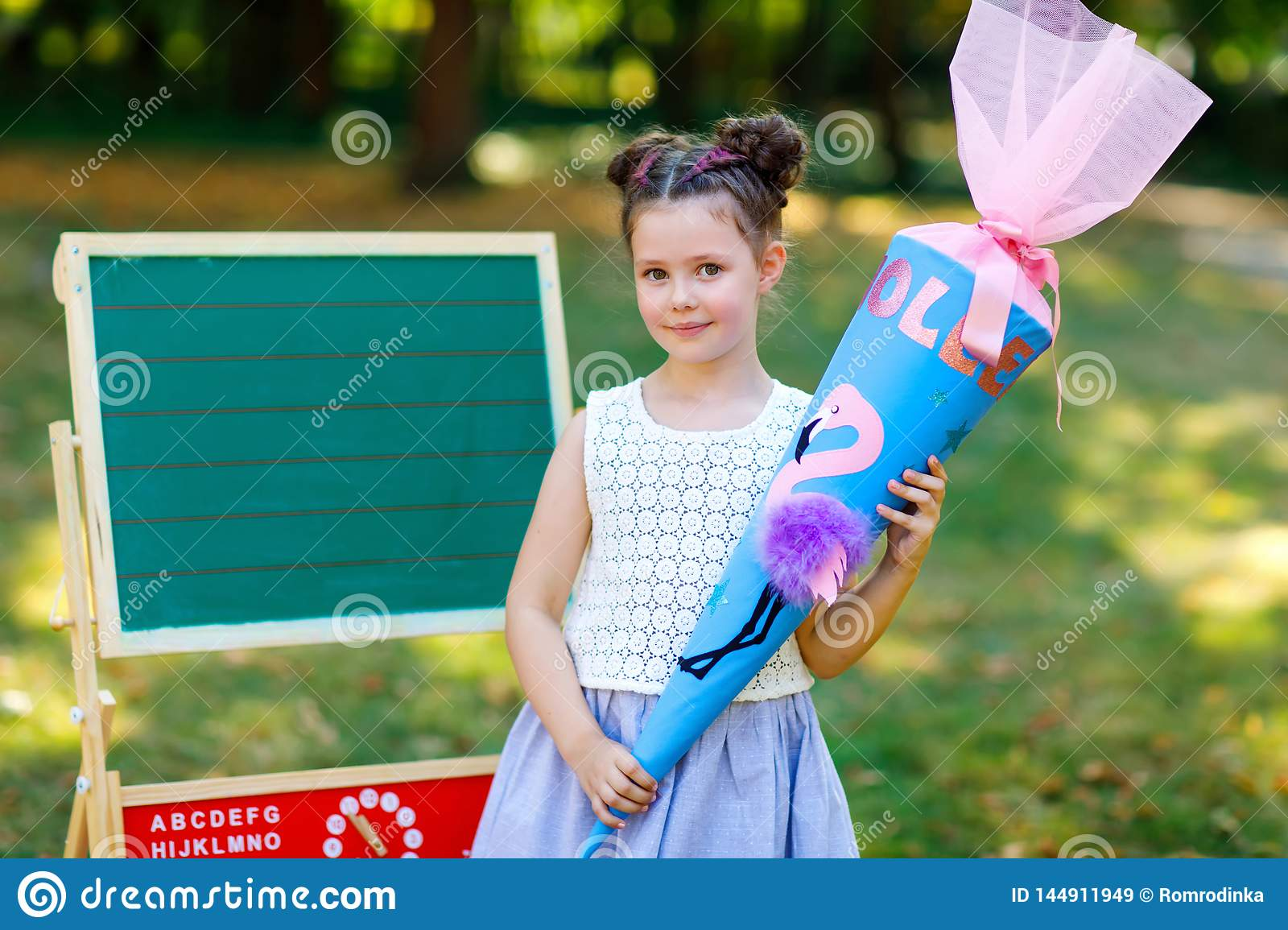 Happy little kid girl by desk with backpack or satchel and big school bag or cone traditional in Germany for the first