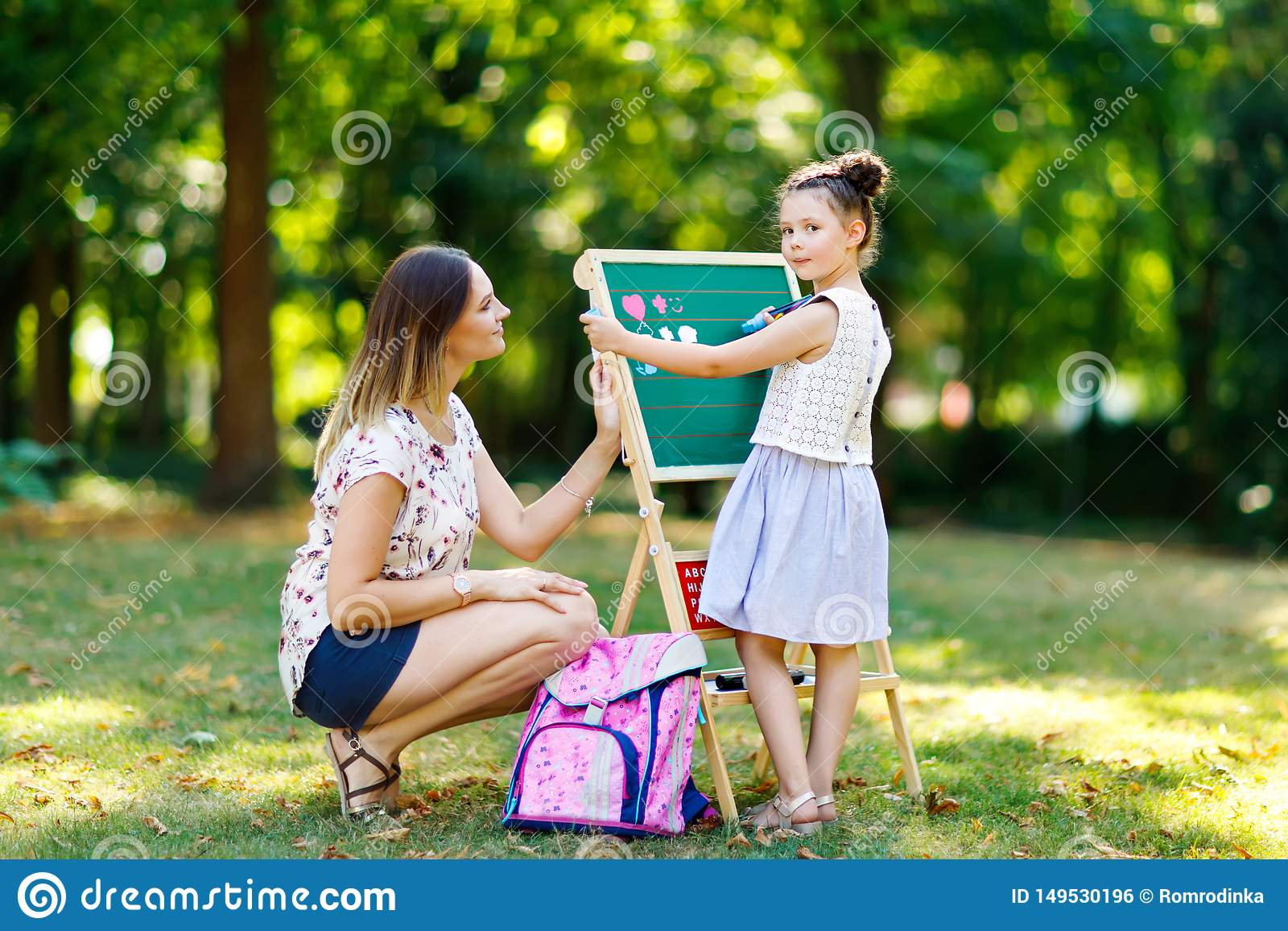 Happy little kid girl and mother by big chalk desk Preschool or schoolkid on first day of elementary class. Back to