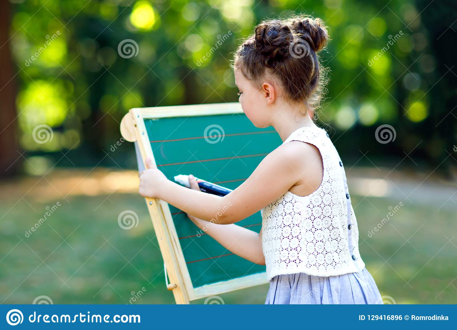 Happy little kid girl standing by big chalk desk Preschool or schoolkid on first day of elementary class. Back to school