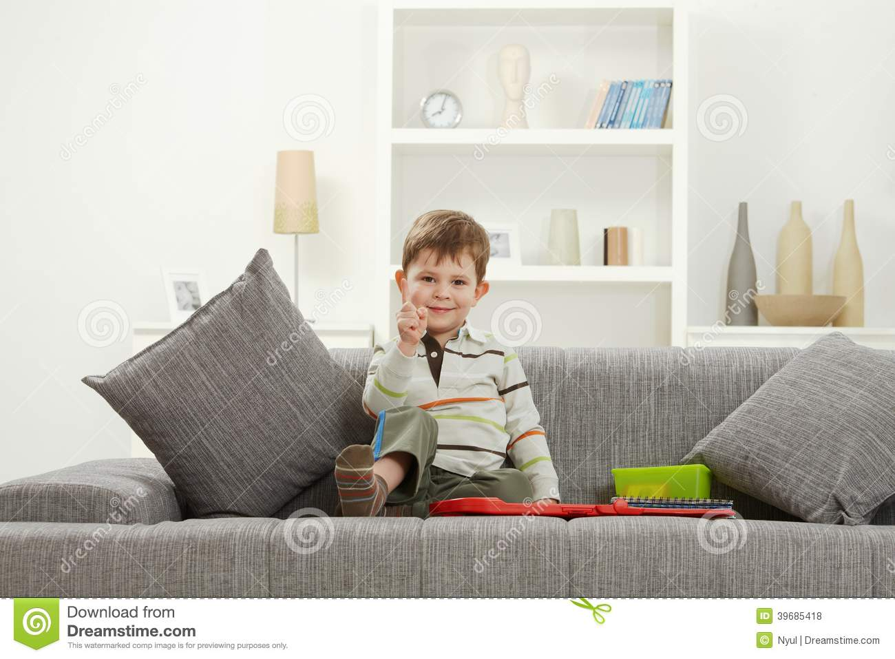Happy Little Kid With Toys Sitting On Sofa Stock Photo