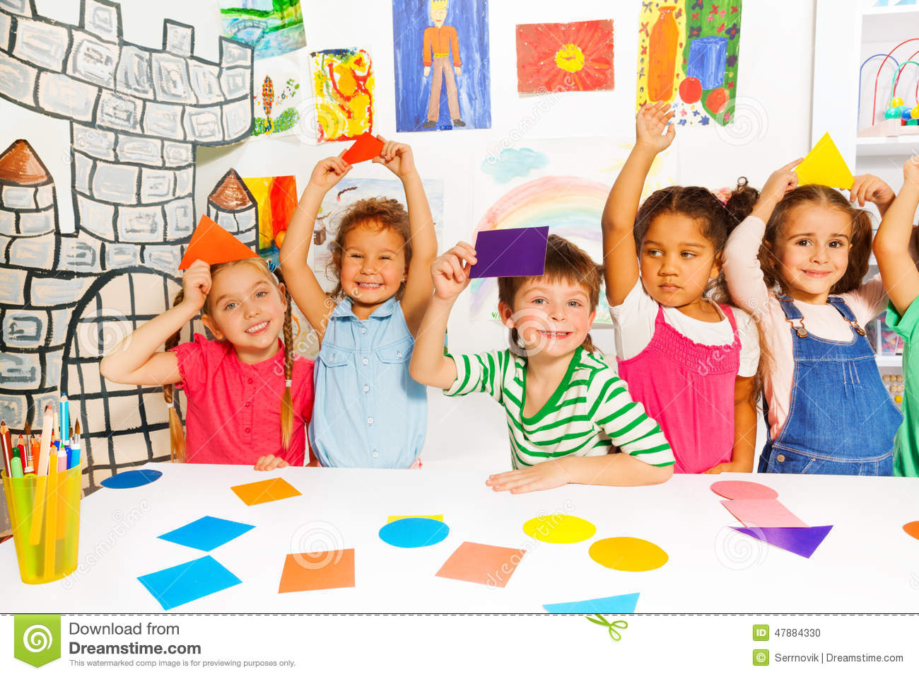 Kinder Garden: Happy Little Kids With Color Cardboard Shapes Stock Photo
