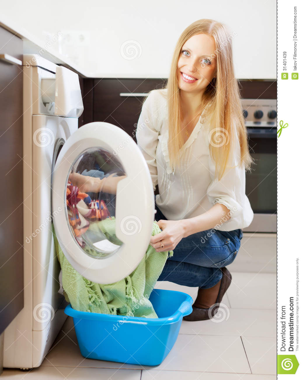 Washing Machine With Clothes ~ Happy long haired woman loading clothes into washing