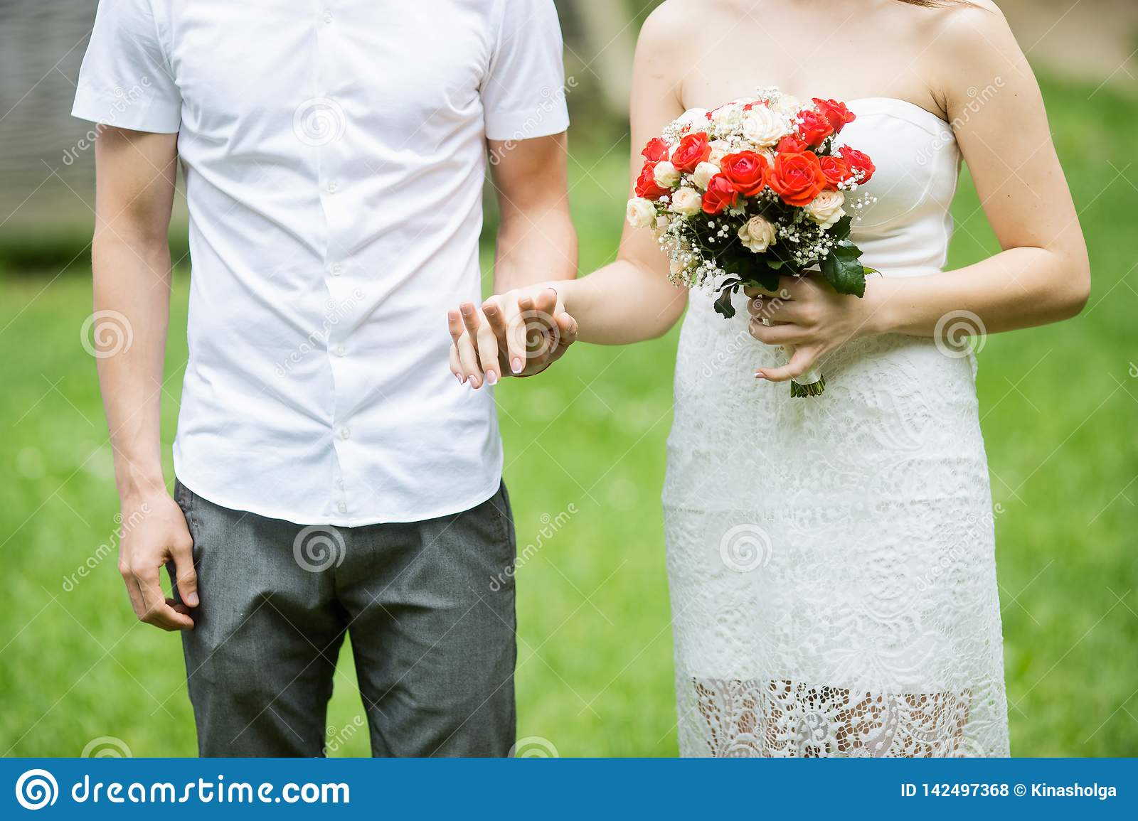Happy married couple holding hands outdoor with flowers
