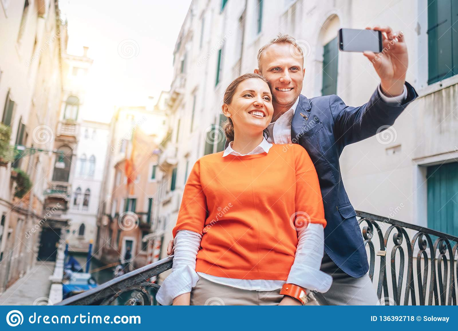 Happy in love couple take selfie photo on one of numerous bridge in Venice, Italy. Traveling to