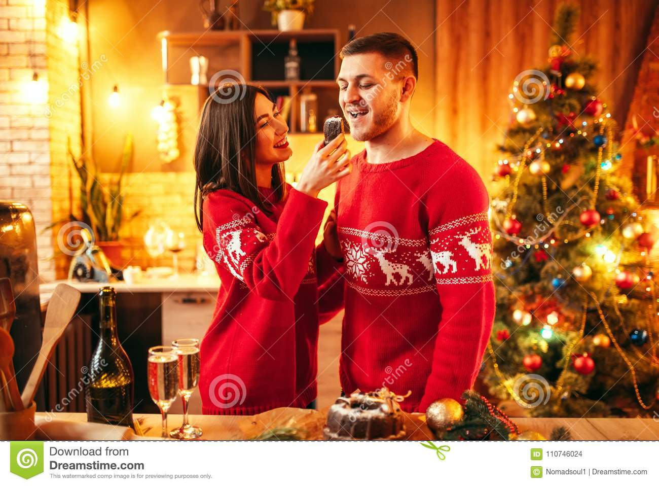 A Husband For Christmas.Wife Is Feeding Her Husband A Christmas Cake Stock Photo